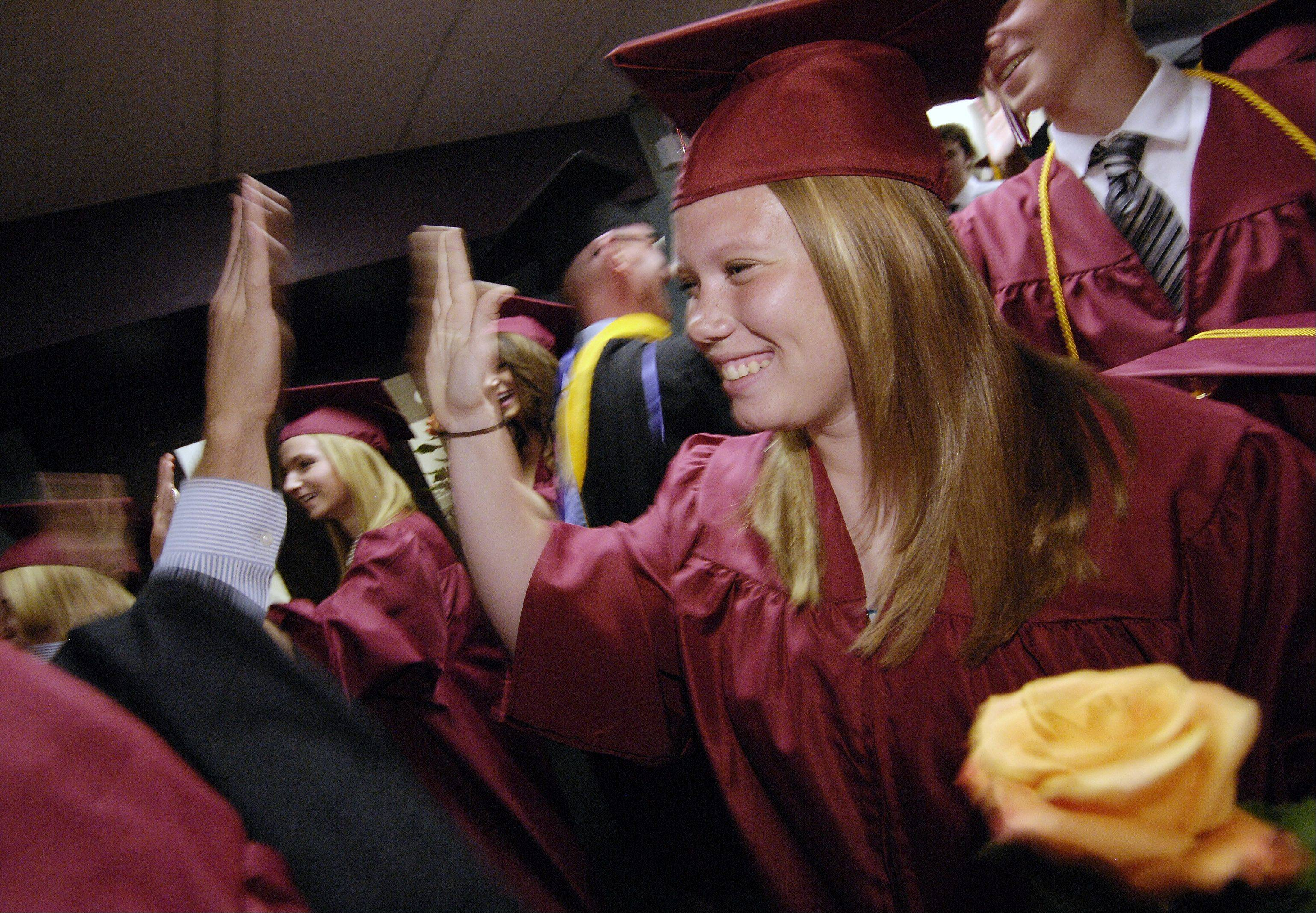 Emily Hillstron high fives faculty members as they make their way through the line of graduates before the start of the Wheaton Academy graduation, Sunday.