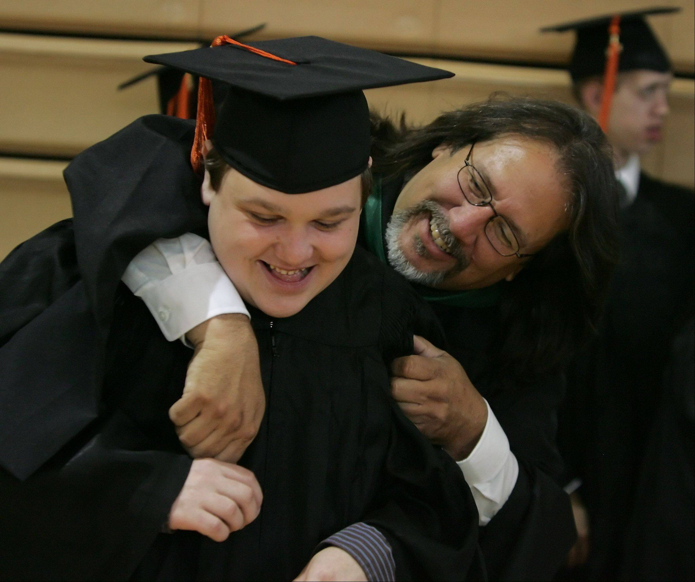 Special education teacher Craig Ameel gives graduate Chris Petrik a hug before the John Hersey High School graduation on Sunday at the school in Arlington Heights. The school was celebrating its 43rd commencement exercises