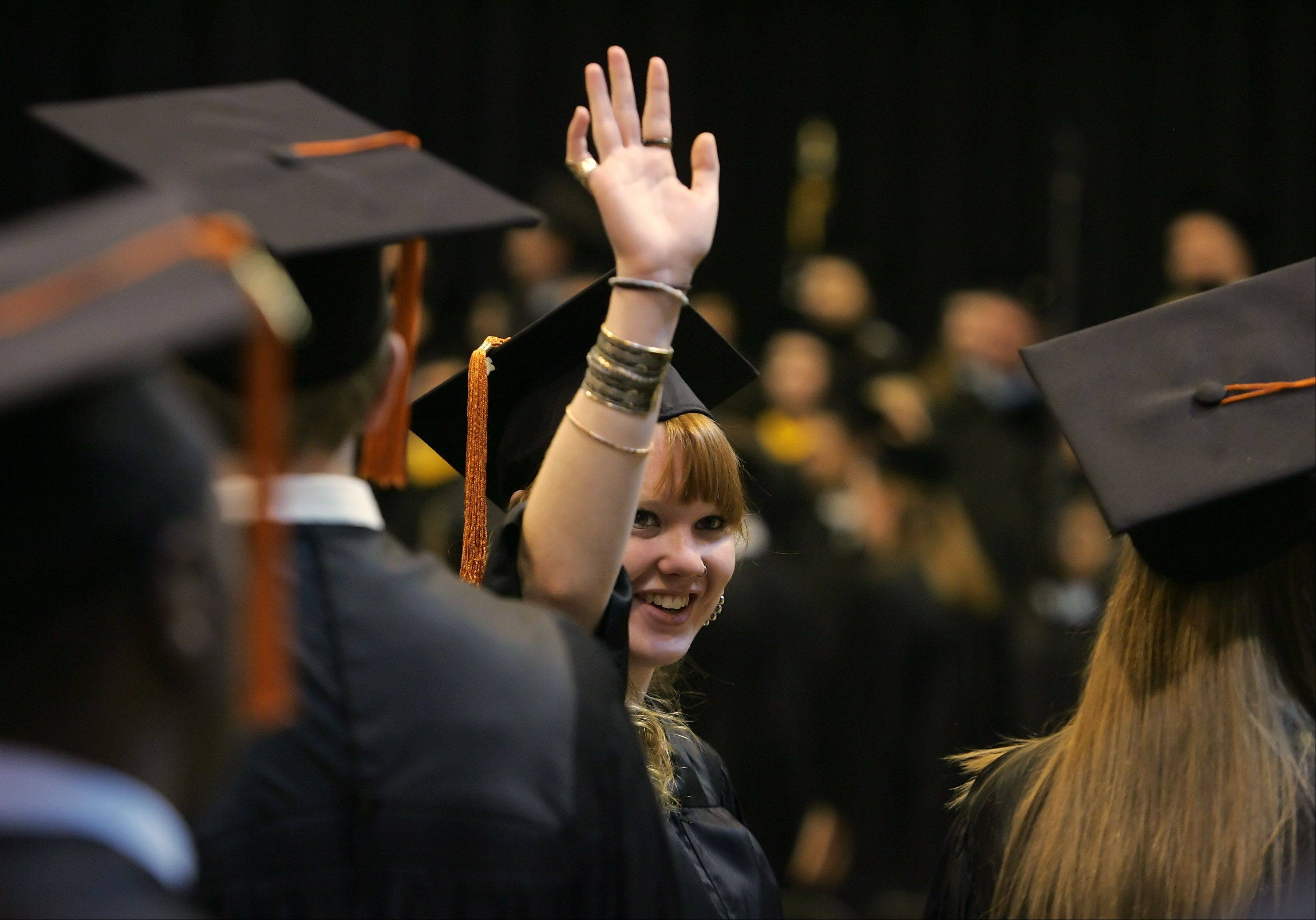 Constance Heuer waves to family members during the John Hersey High School graduation on Sunday at the school in Arlington Heights. The school was celebrating its 43rd commencement exercises