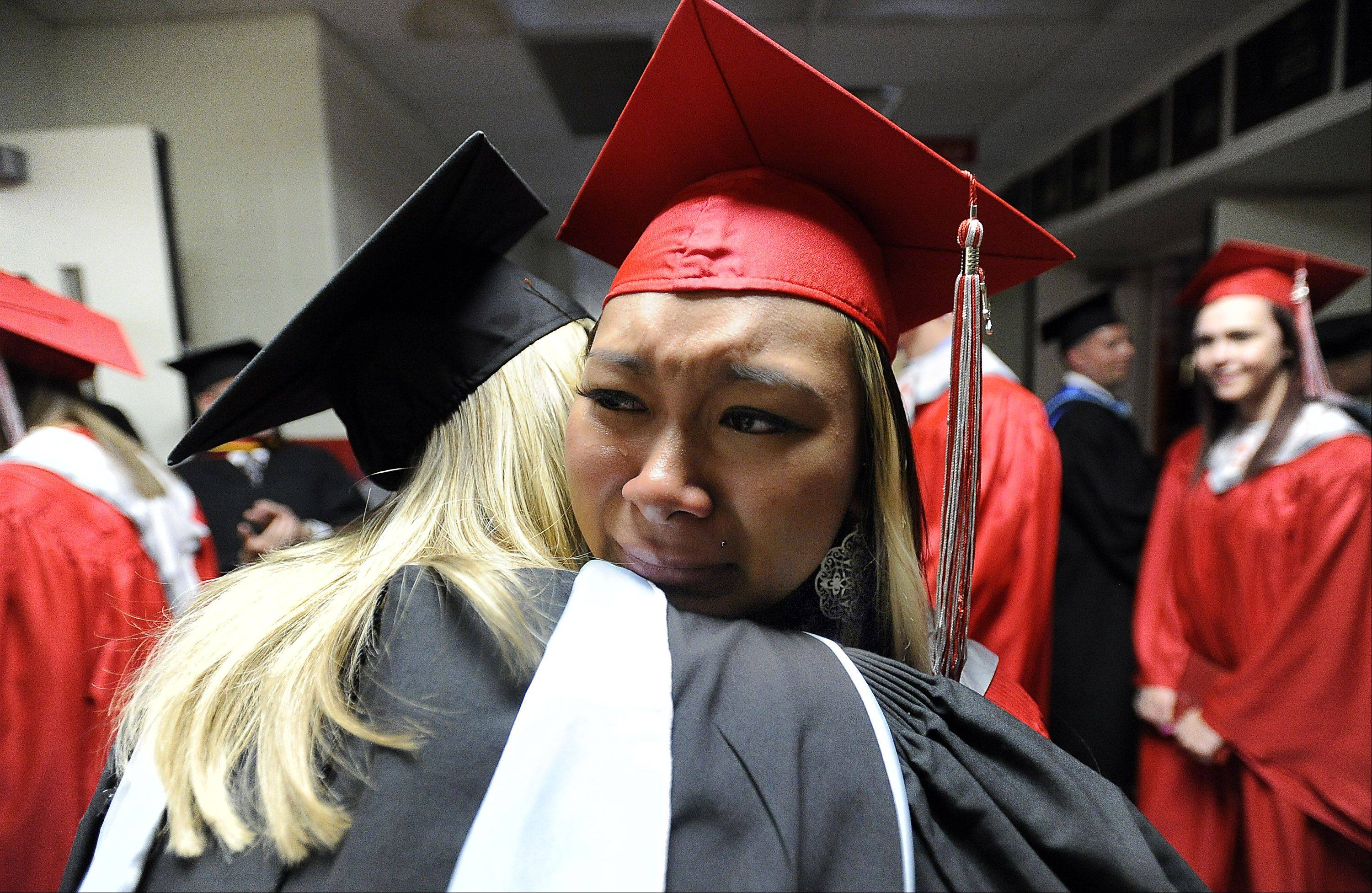 Palatine's Aileen Hong is in tears as she hugs teacher Jessica Means at Palatine High School's graduation ceremony on Sunday.