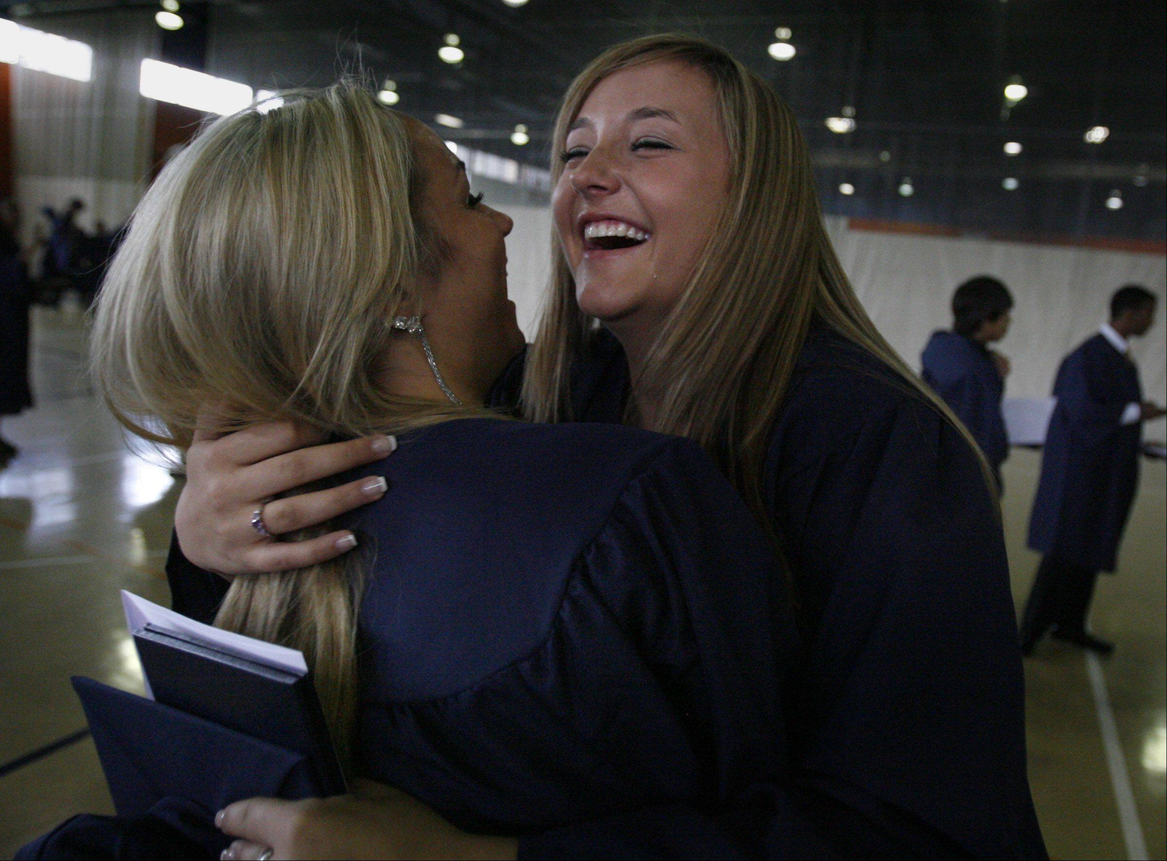 Buffalo Grove High School graduates Kathy Hampton, right, gets a hug from Malinda Lacy, after the school's ceremony in Buffalo Grove Sunday.