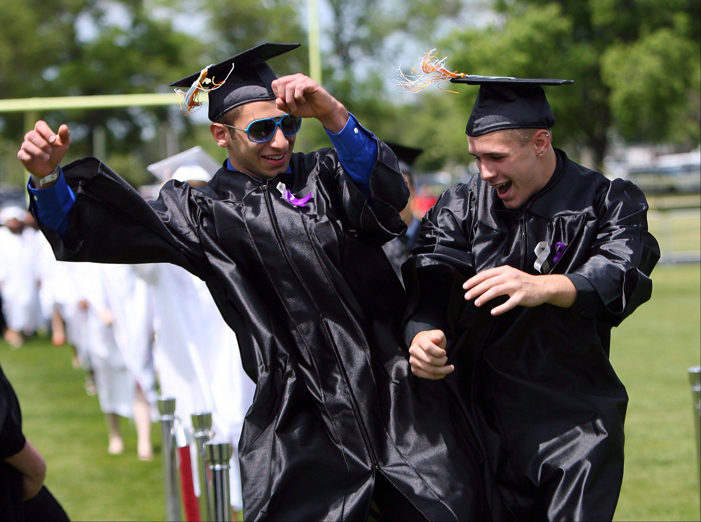 Jodan Pessah, left, and Steven Carlson celebrate as they enter the football field during the Maine West High School graduation ceremony Sunday in Des Plaines.