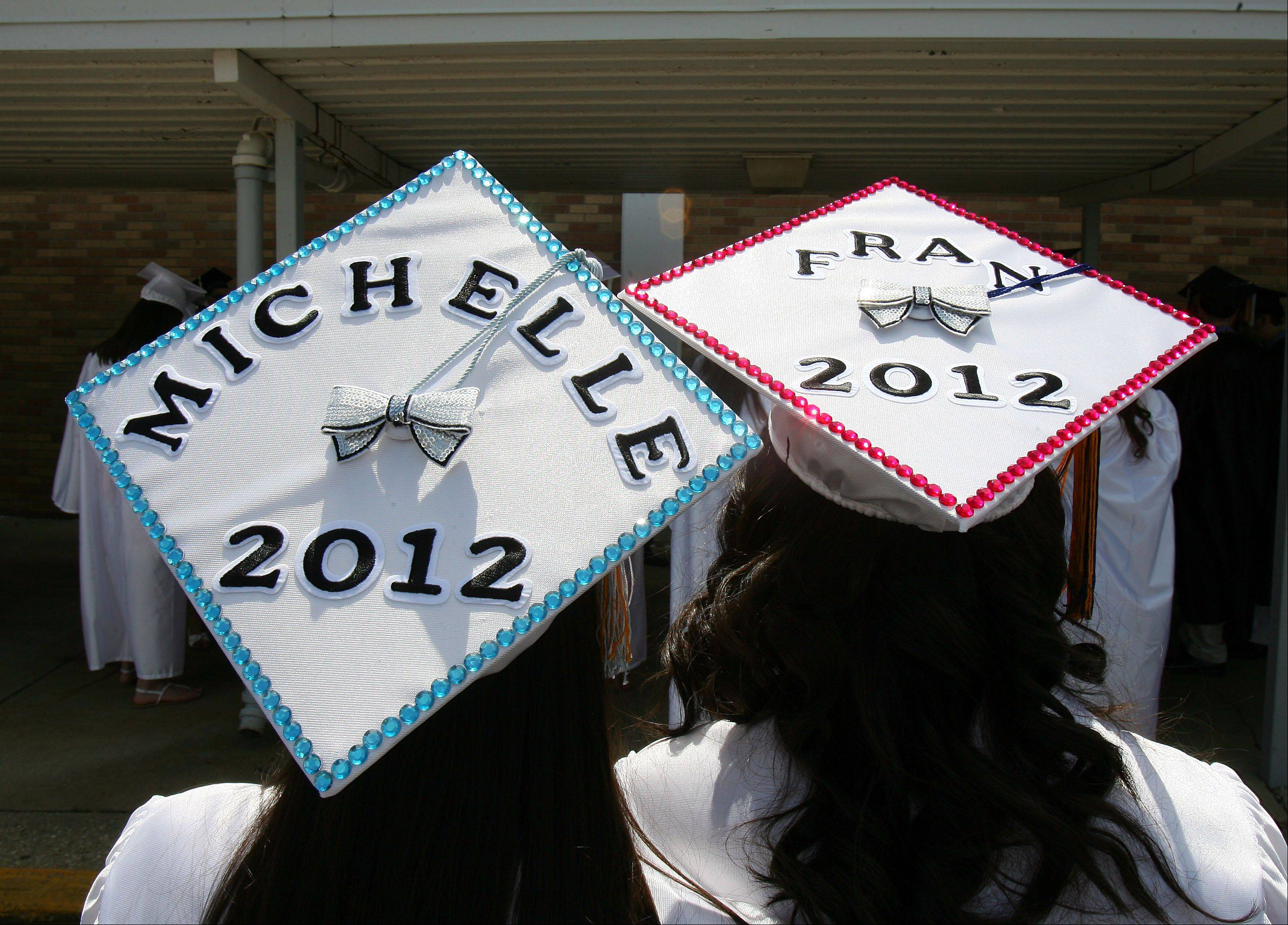 Michelle Madalinski and Francesca DeCastris show off their decorated caps before Sunday's graduation ceremony at Maine West High School Sunday in Des Plaines.