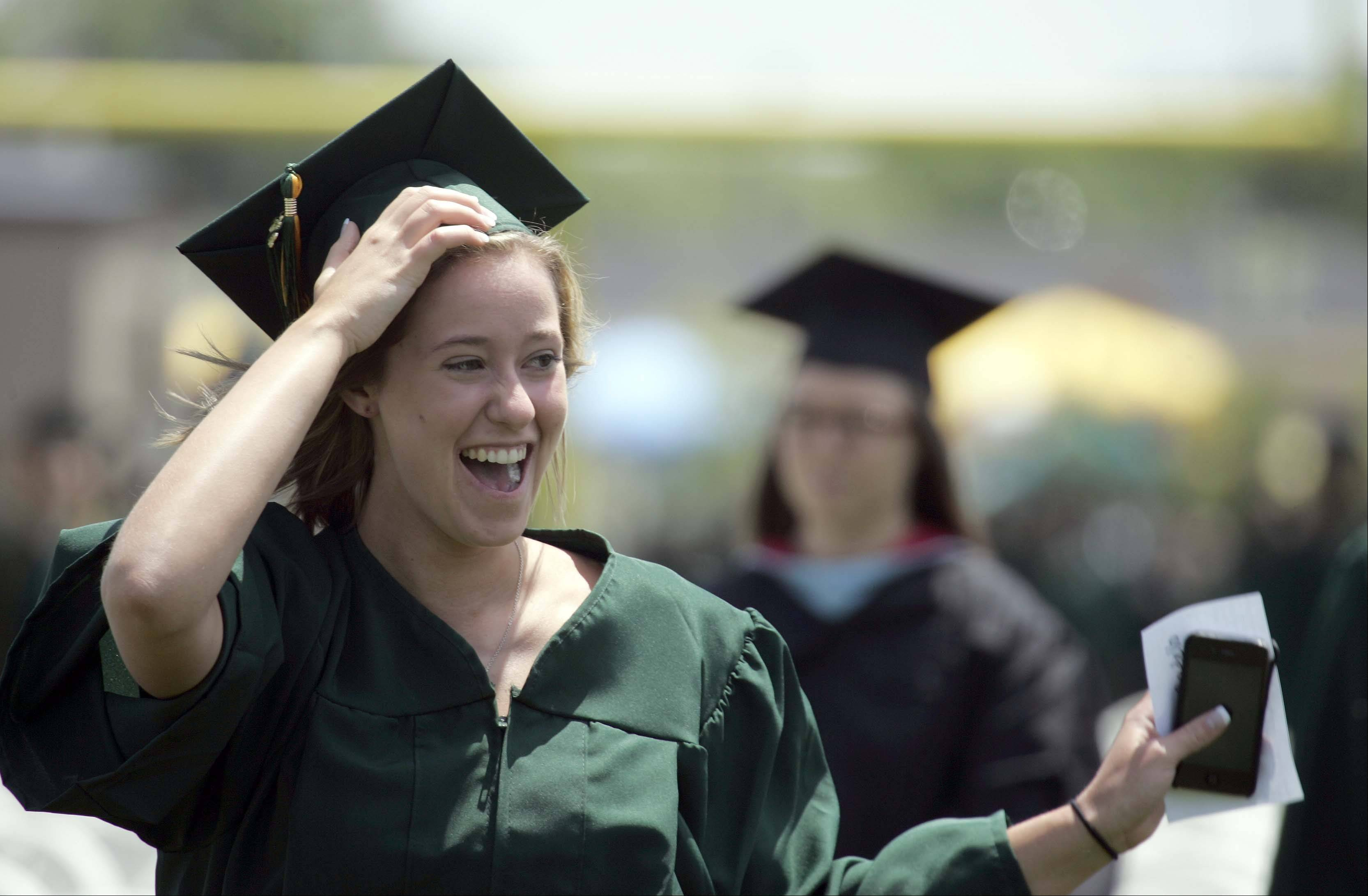 Maryanne Bartello, holds on her mortar board as she waves to her family during the Elk Grove High School graduation ceremony Sunday June 3, 2012.