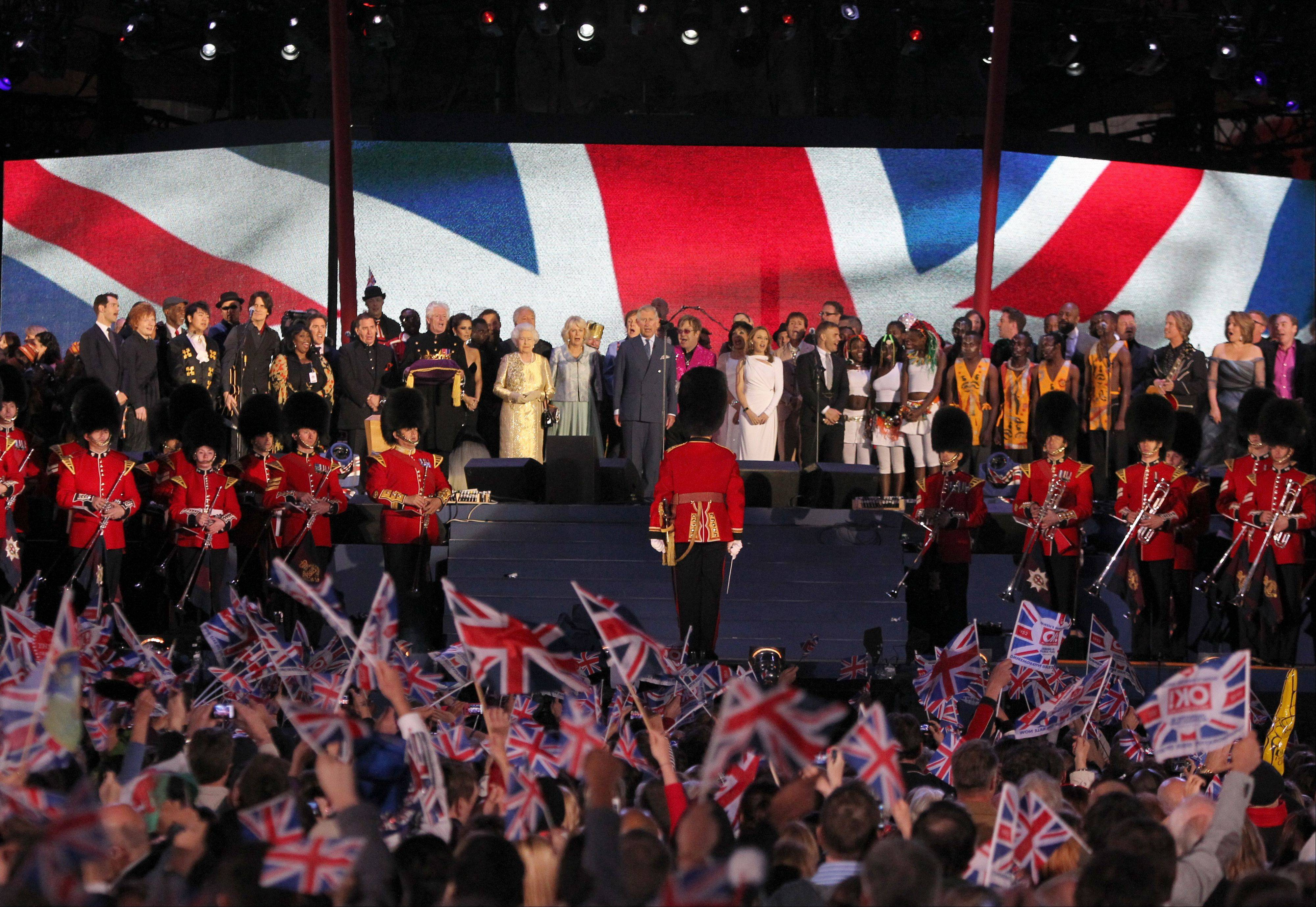 Britain's Prince Charles, centre, Camilla, Duchess of Cornwall, and Britain's Queen Elizabeth II, centre left, are joined on stage by performers at the conclusion of the Queen's Jubilee Concert in front of Buckingham Palace, London, Monday, June 4, 2012. The concert is a part of four days of celebrations to mark the 60-year reign of Britain's Queen Elizabeth II.