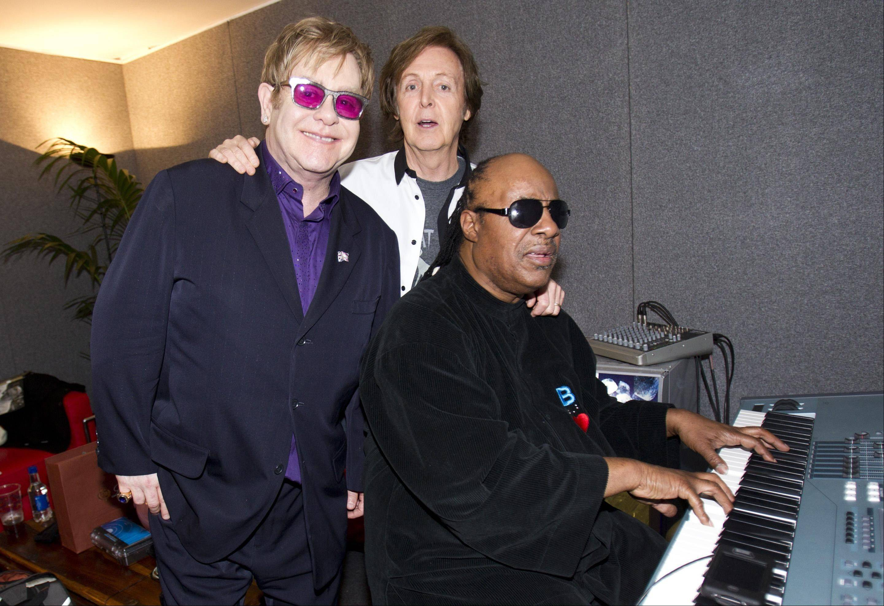 In this photo released by MPL Communications , Sir Paul McCartney with Sir Elton John and Stevie Wonder backstage the Diamond Jubilee concert at Buckingham Palace, in London Monday June 4, 2012.