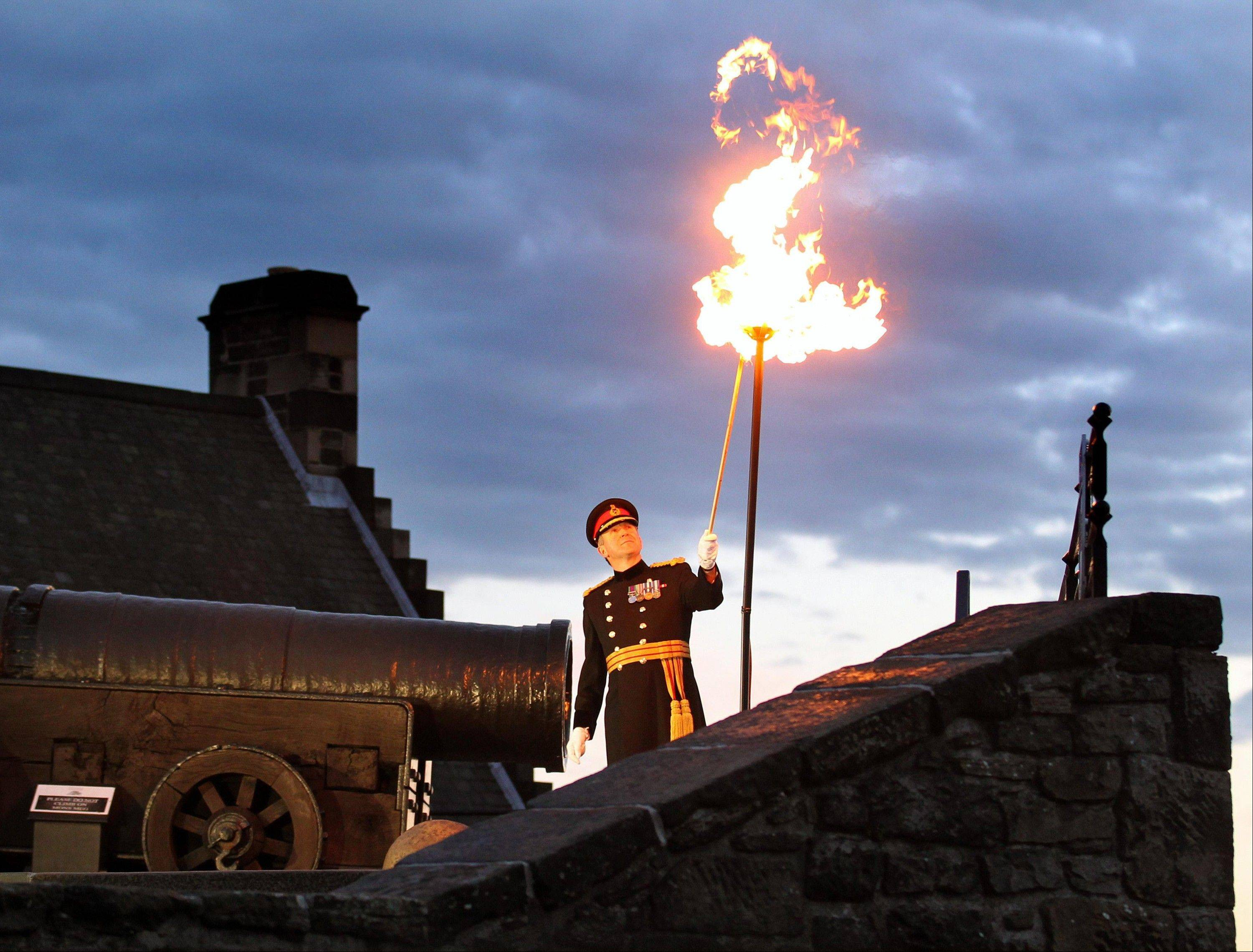 Major General Nick Eeles, Governor of Edinburgh Castle and General Officer Commanding Scotland, lights the Diamond Jubilee beacon at Edinburgh Castle beside Mons Meg Cannon in Edinburgh, Monday June 4, 2012.