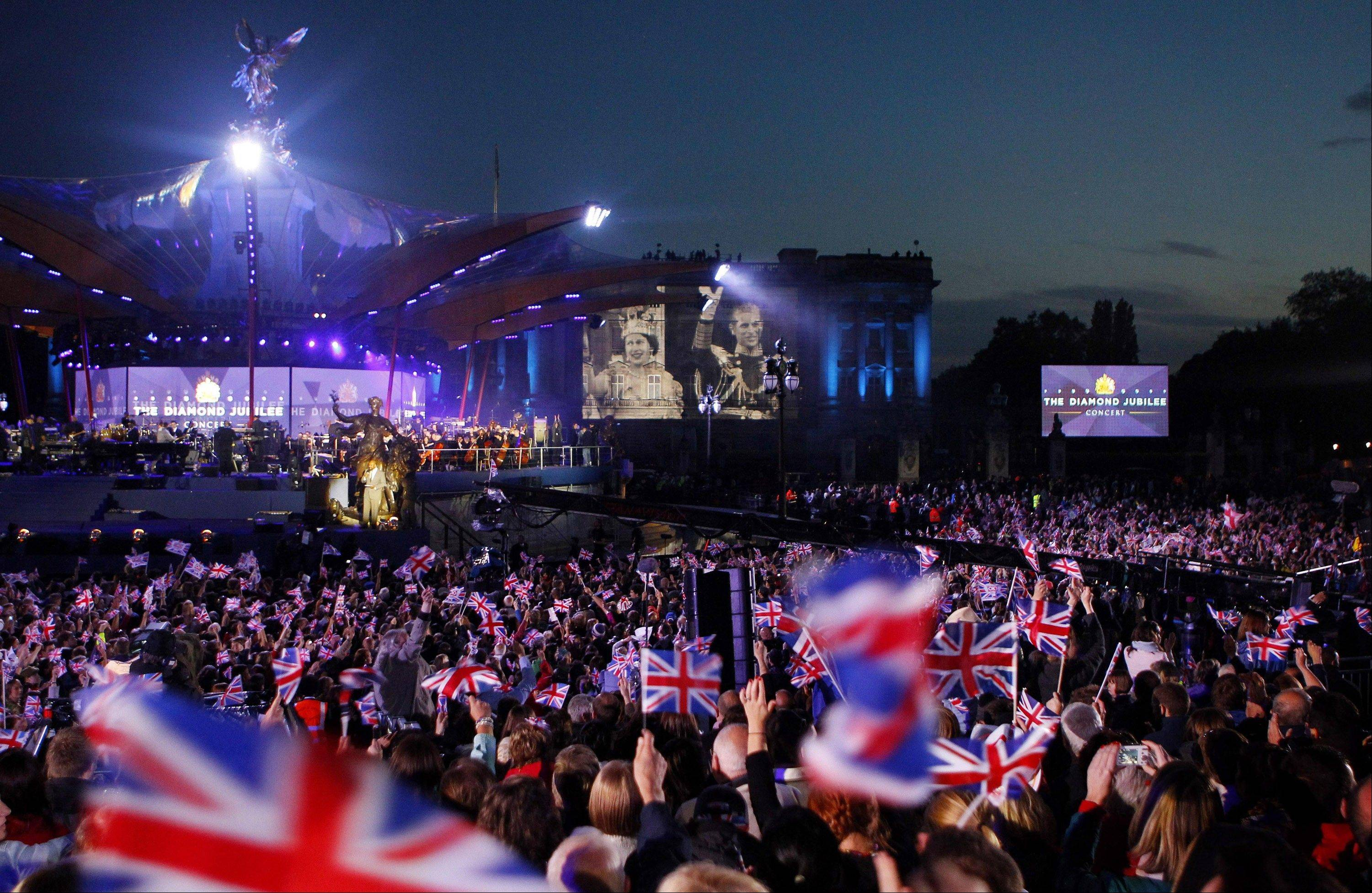 An image of Queen Elizabeth II and Duke of Edinburgh is projected onto Buckingham Palace during the Diamond Jubilee Concert in London Monday, June 4 , 2012.