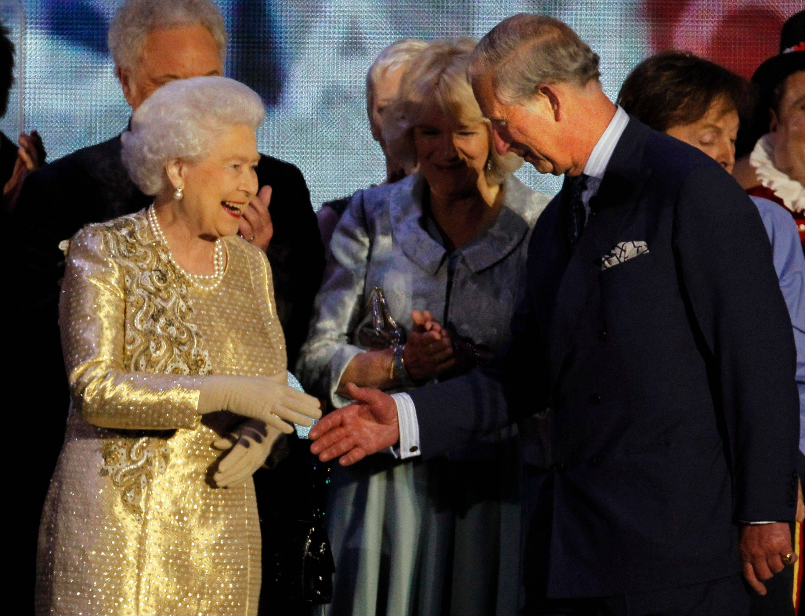 Britain's Queen Elizabeth II shakes the hand of her son Prince Charles at the end of the Queen's Jubilee Concert in front of Buckingham Palace, London, Monday, June 4, 2012. The concert is a part of four days of celebrations to mark the 60-year reign of Britain's Queen Elizabeth II.