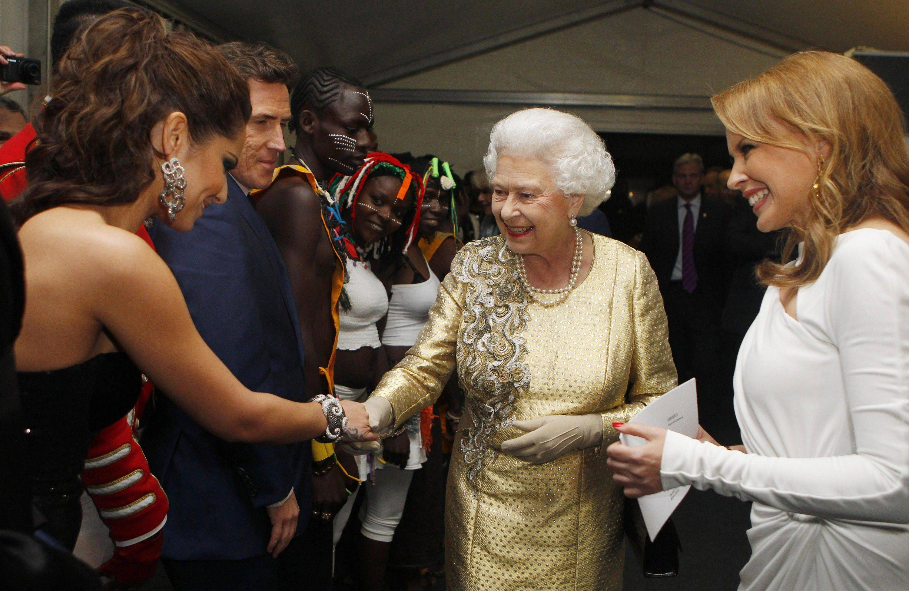 Queen Elizabeth II, center, meets Cheryl Cole backstage at the Diamond Jubilee Concert outside Buckingham Palace in London Monday, June 4, 2012.