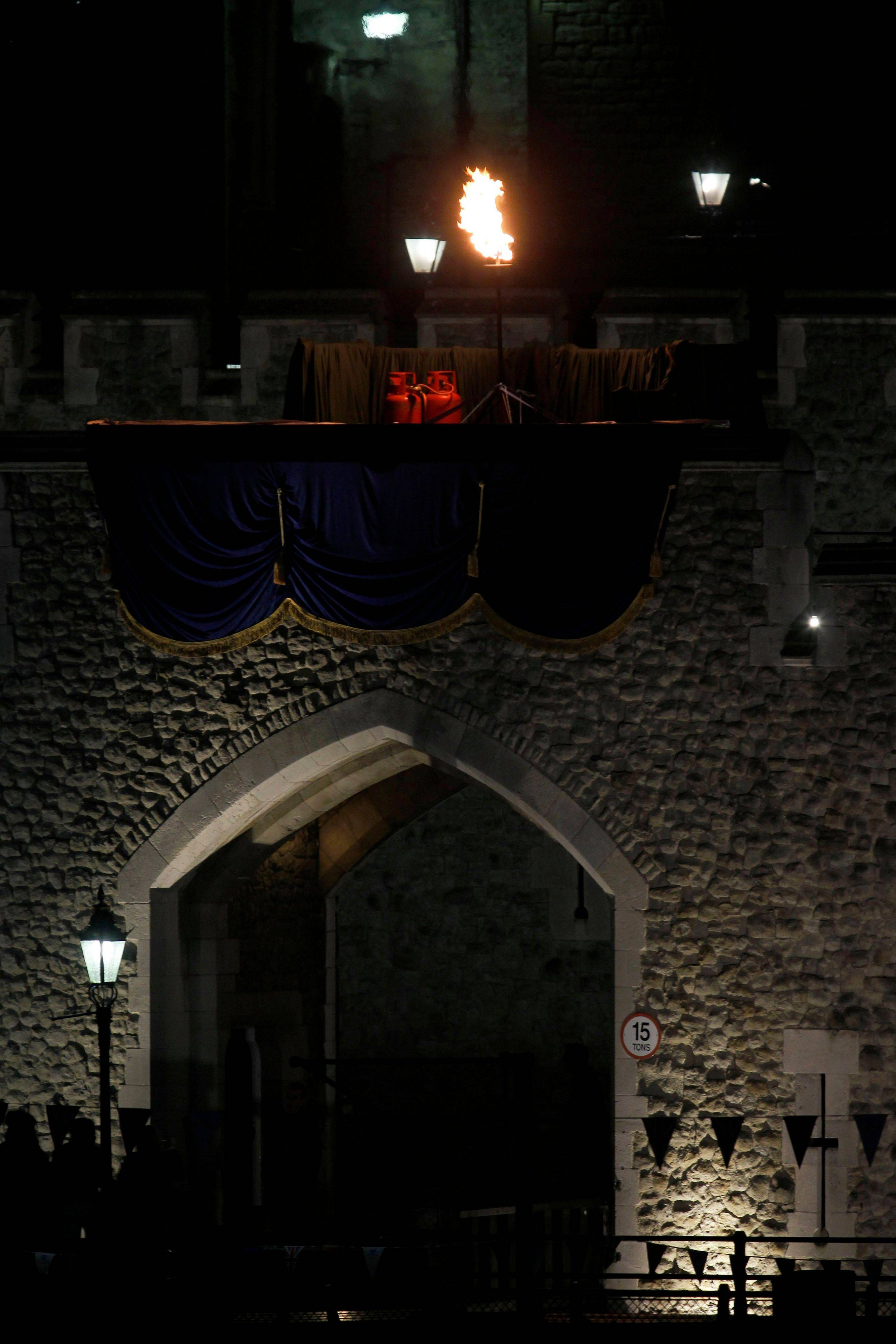 A beacon is lit on the battlements of the Tower of London as part of a four-day Diamond Jubilee celebration to mark the 60th anniversary of Queen Elizabeth II accession to the throne, London, Monday, June 4, 2012.