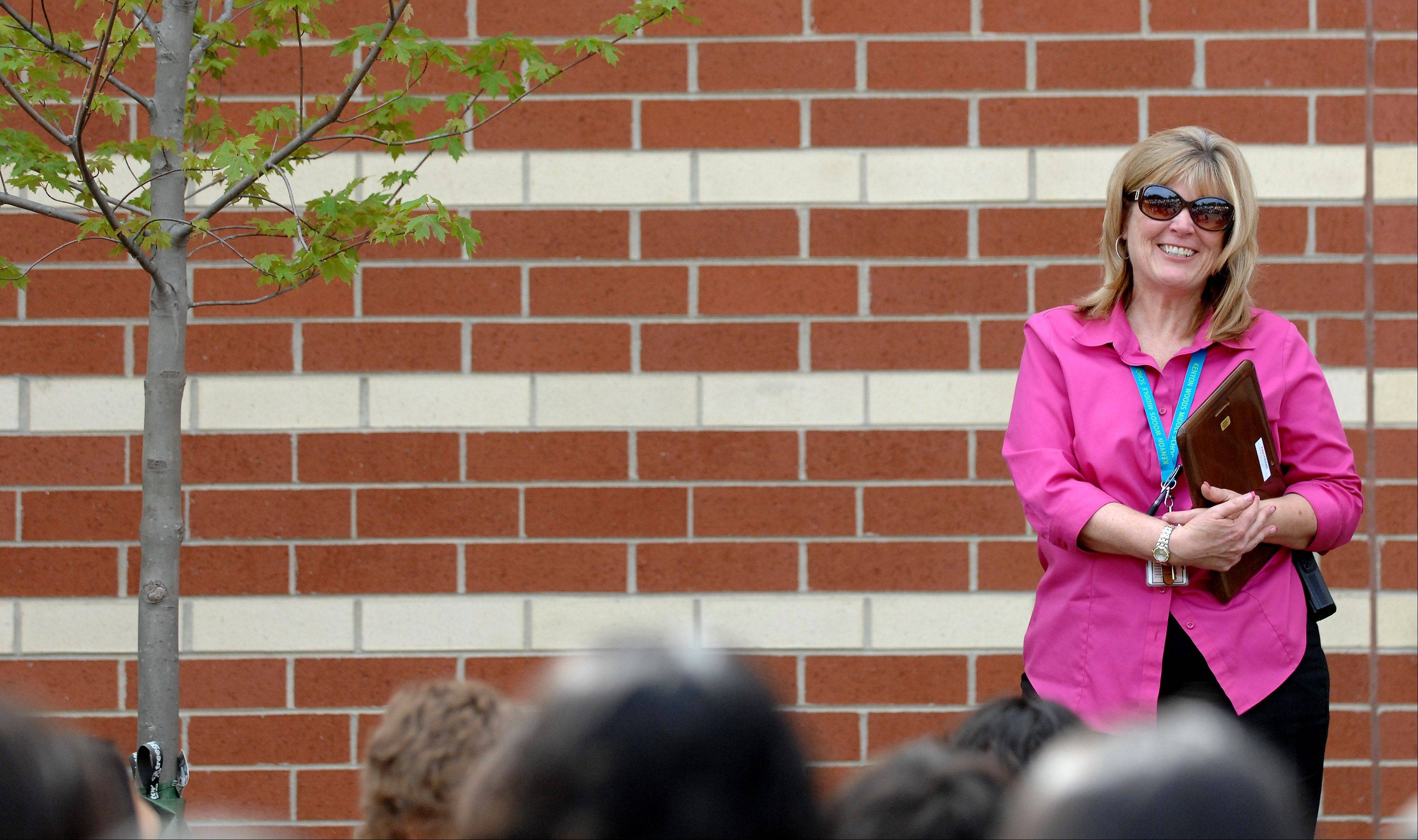 Kenyon Woods Middle School Principal Sue Welu smiles at the applause she gets from students during a ceremony Monday dedicating a tree in honor of her retirement.