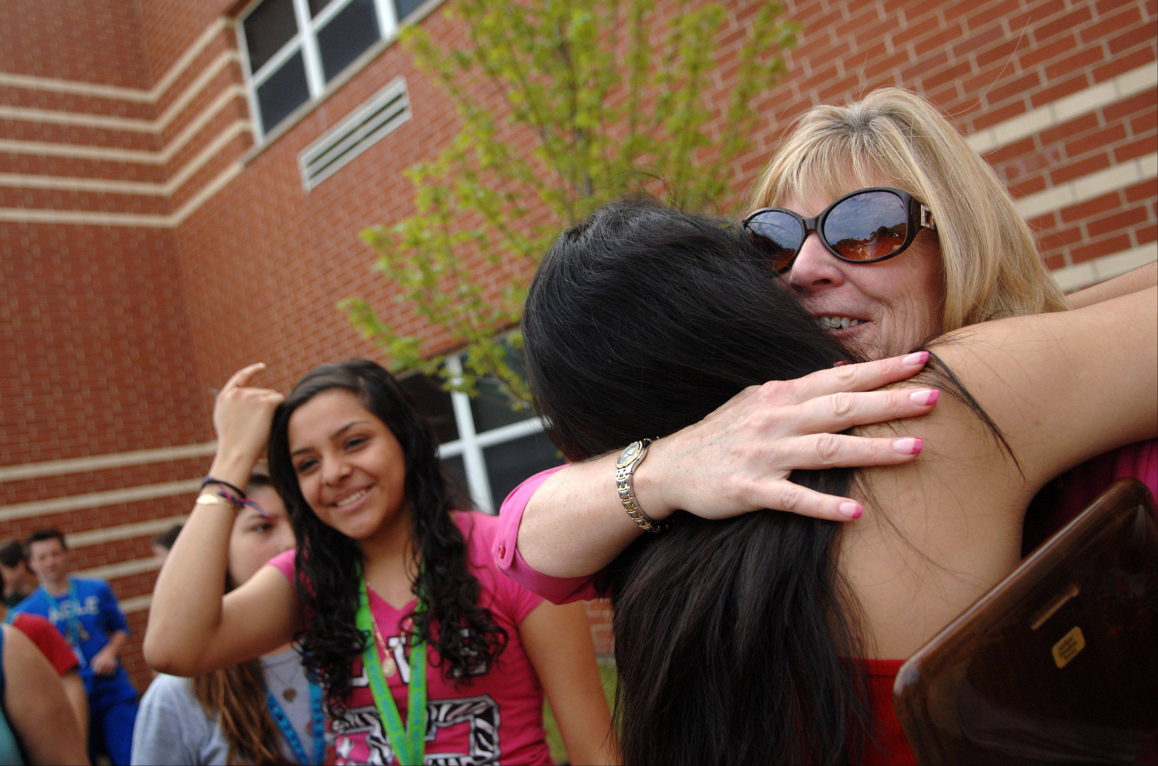 Kenyon Woods Middle School Principal Sue Welu gets hugs from students after a ceremony for her retirement at the school in South Elgin Monday. The PTO had a maple tree planted in her honor in front of the school.