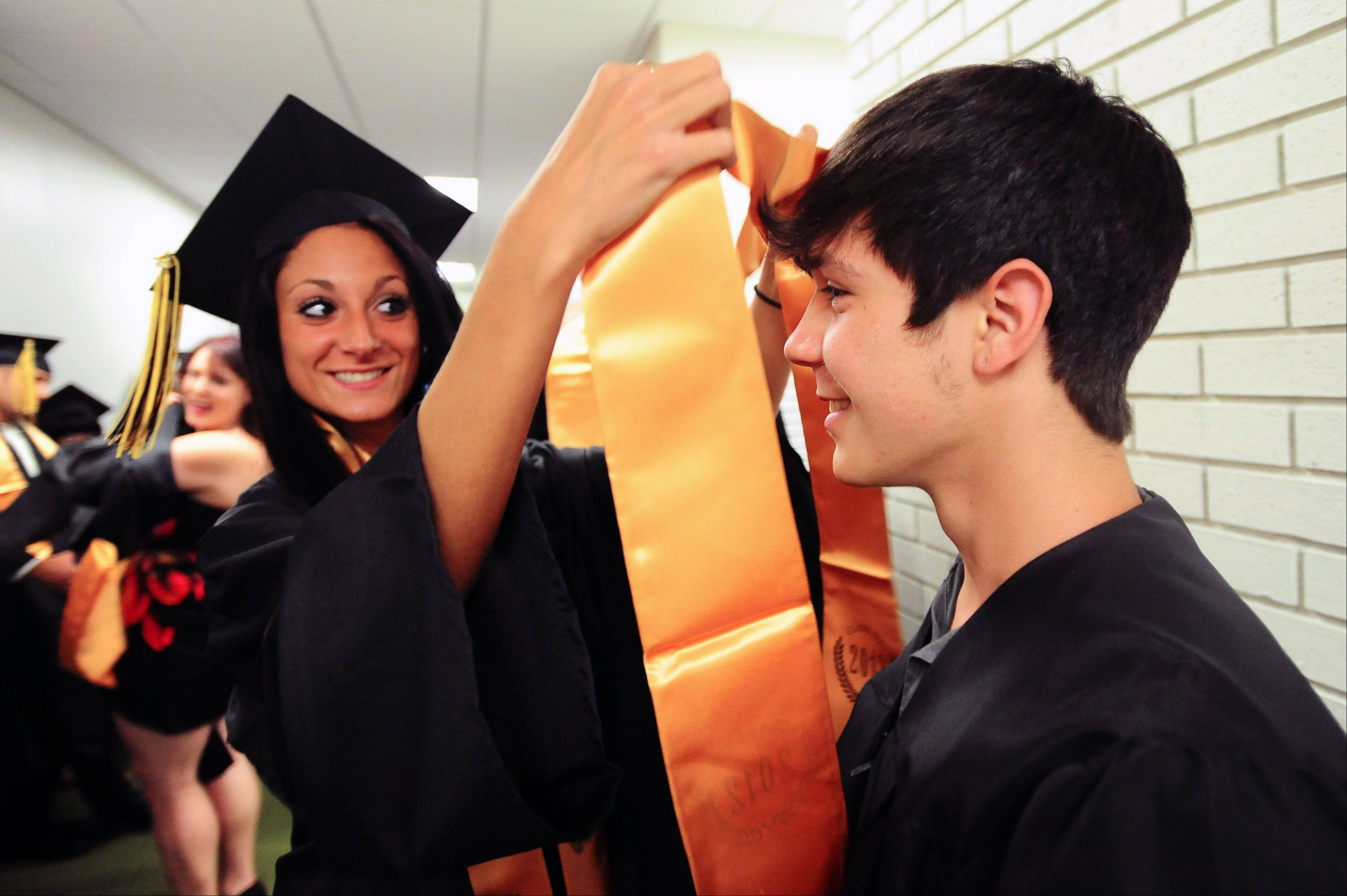 Alex Bender helps Ivan Mercado get ready for the 2012 Glenbard North High School senior class commencement on Sunday.