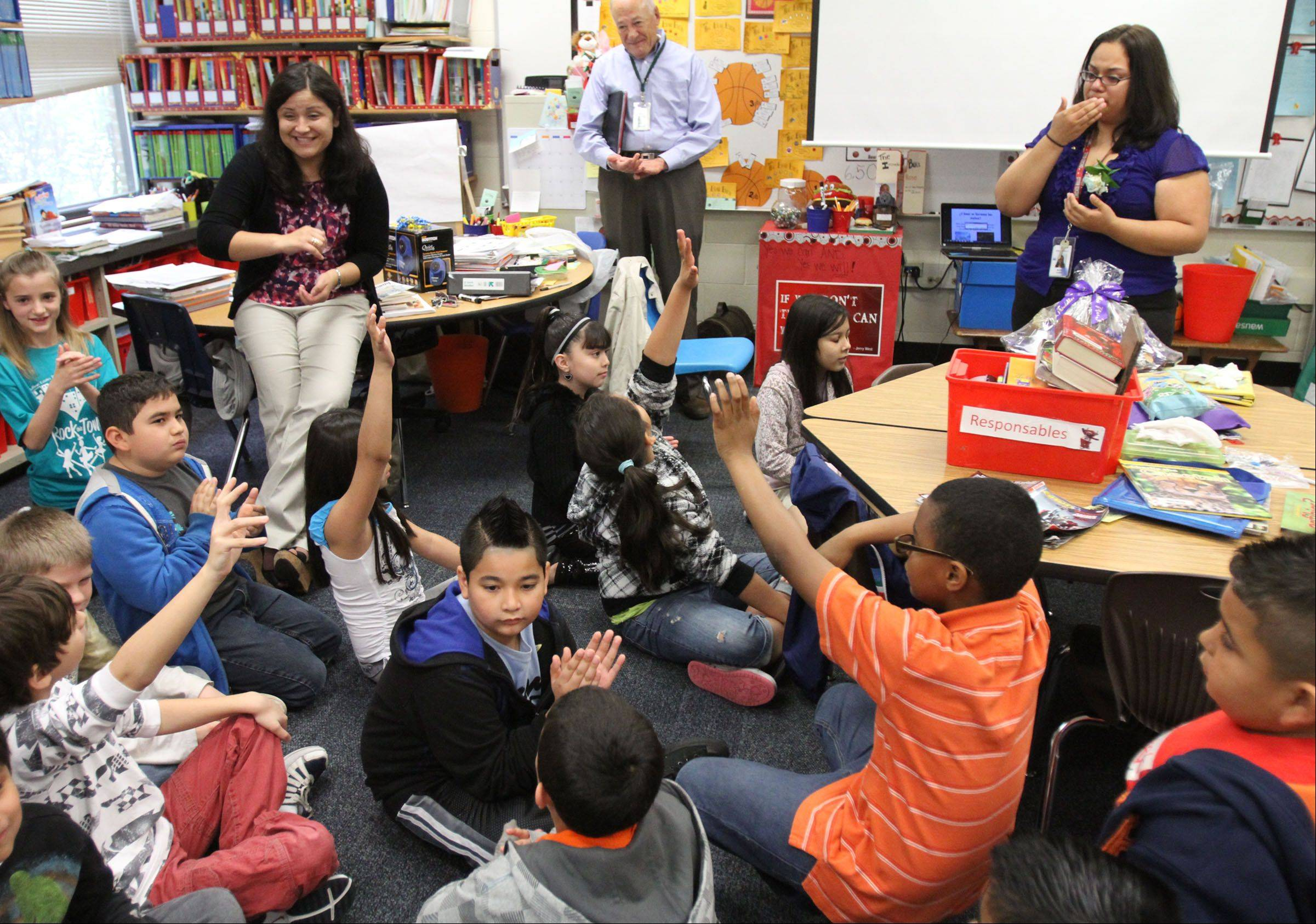 Maria Barba, bilingual teacher at Douglas MacArthur Elementary School in Hoffman Estates, listens to her students say why she is a great teacher after being surprised with a Golden Apple Award.