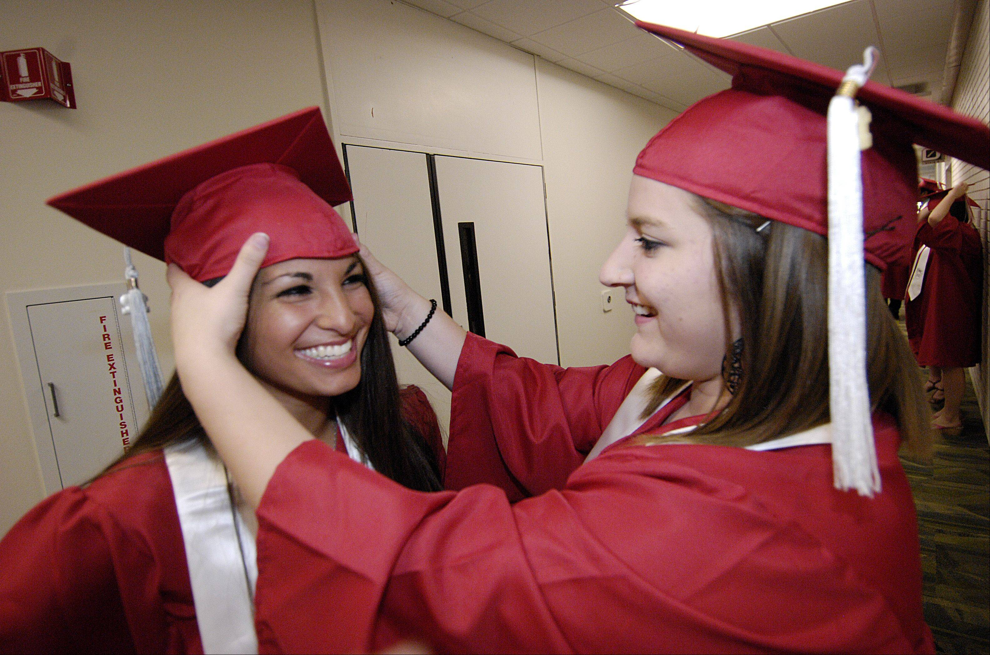 Alexis Parson and Courtney Heneghan get ready for the Glenbard East High School graduation Sunday June 3 at the College of DuPage in Glen Ellyn.