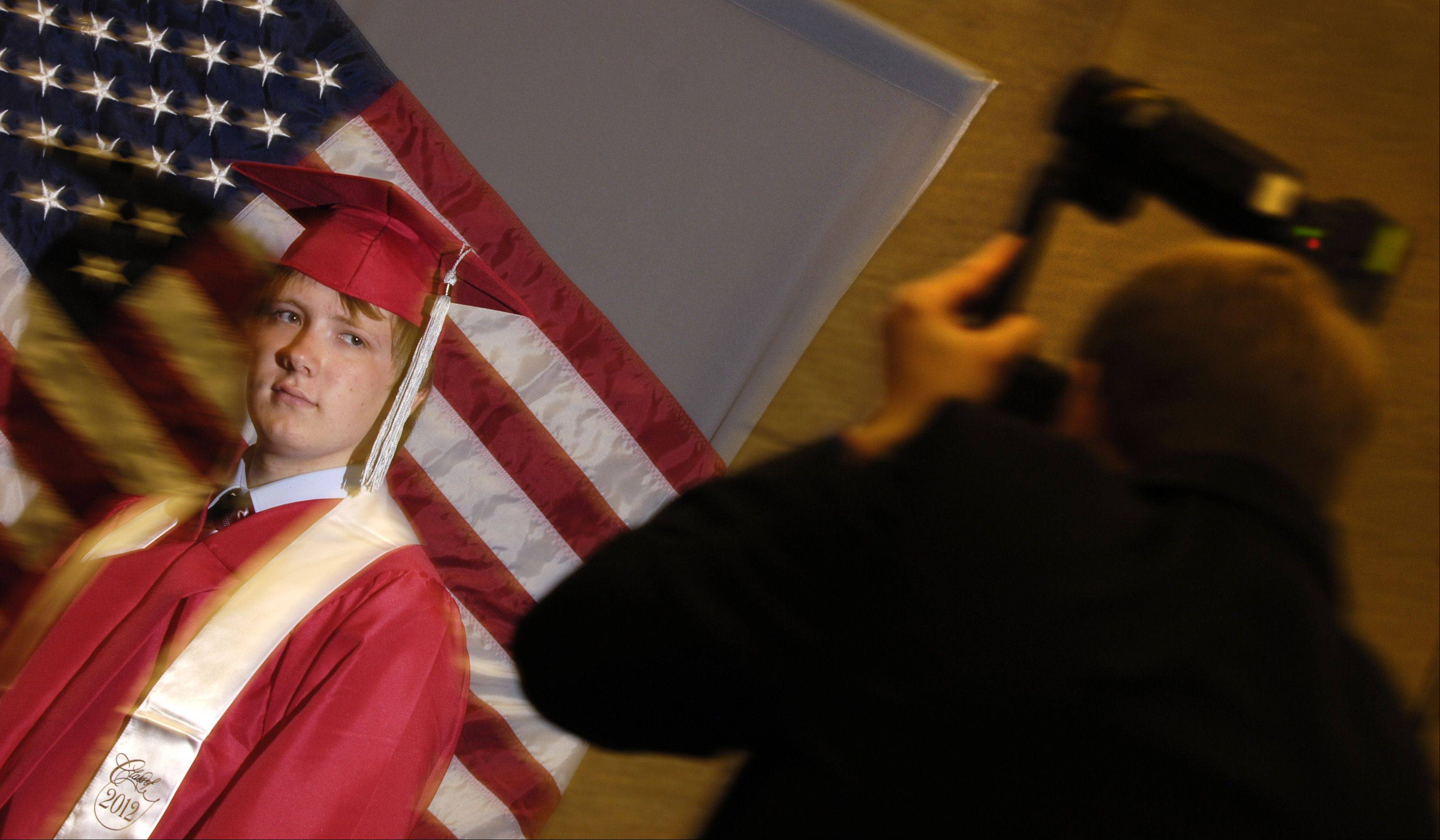 Raymond Ziecina has his photograph taken during the Glenbard East High School graduation ceremony, Sunday June 3 at the College of DuPage in Glen Ellyn.