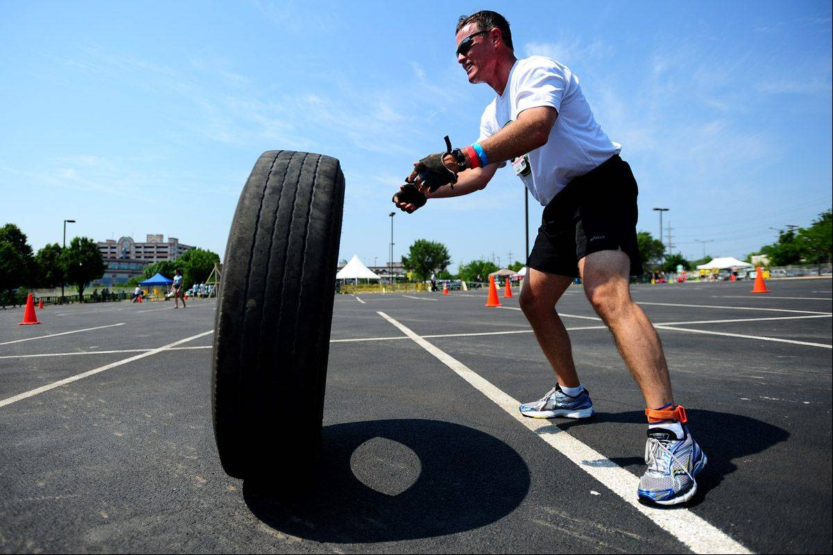 Jim Wilkins of Naperville flips a truck tire over as he finishes a segment of the Amped Up Adventure Race held in Aurora, IL on Sunday.
