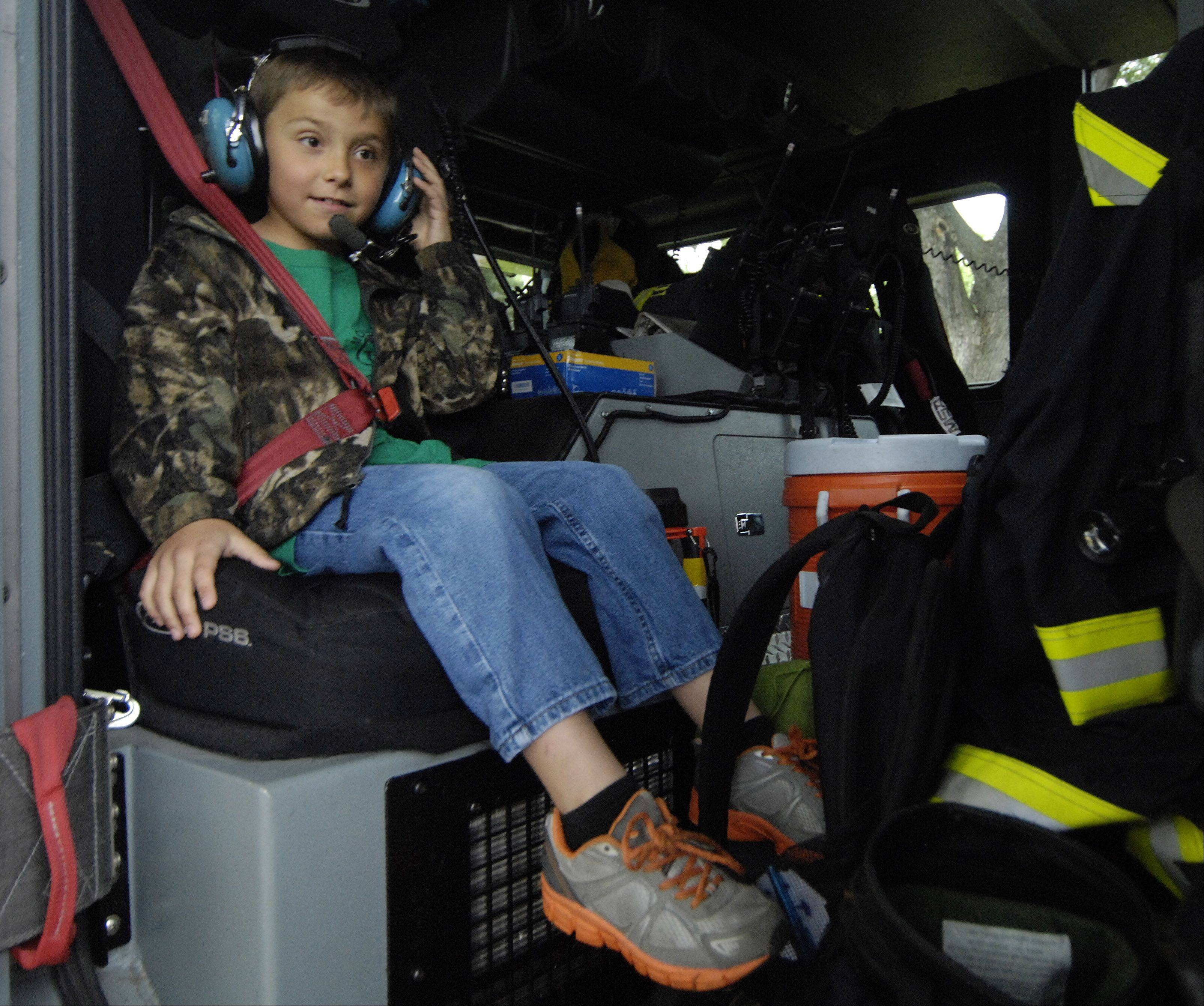 Second grader Carter Jedras is buckled in as he and a friend get a ride on a fire truck to Fairview Elementary School in Mount Prospect Thursday. The opportunity was an auction item for a school fundraiser.
