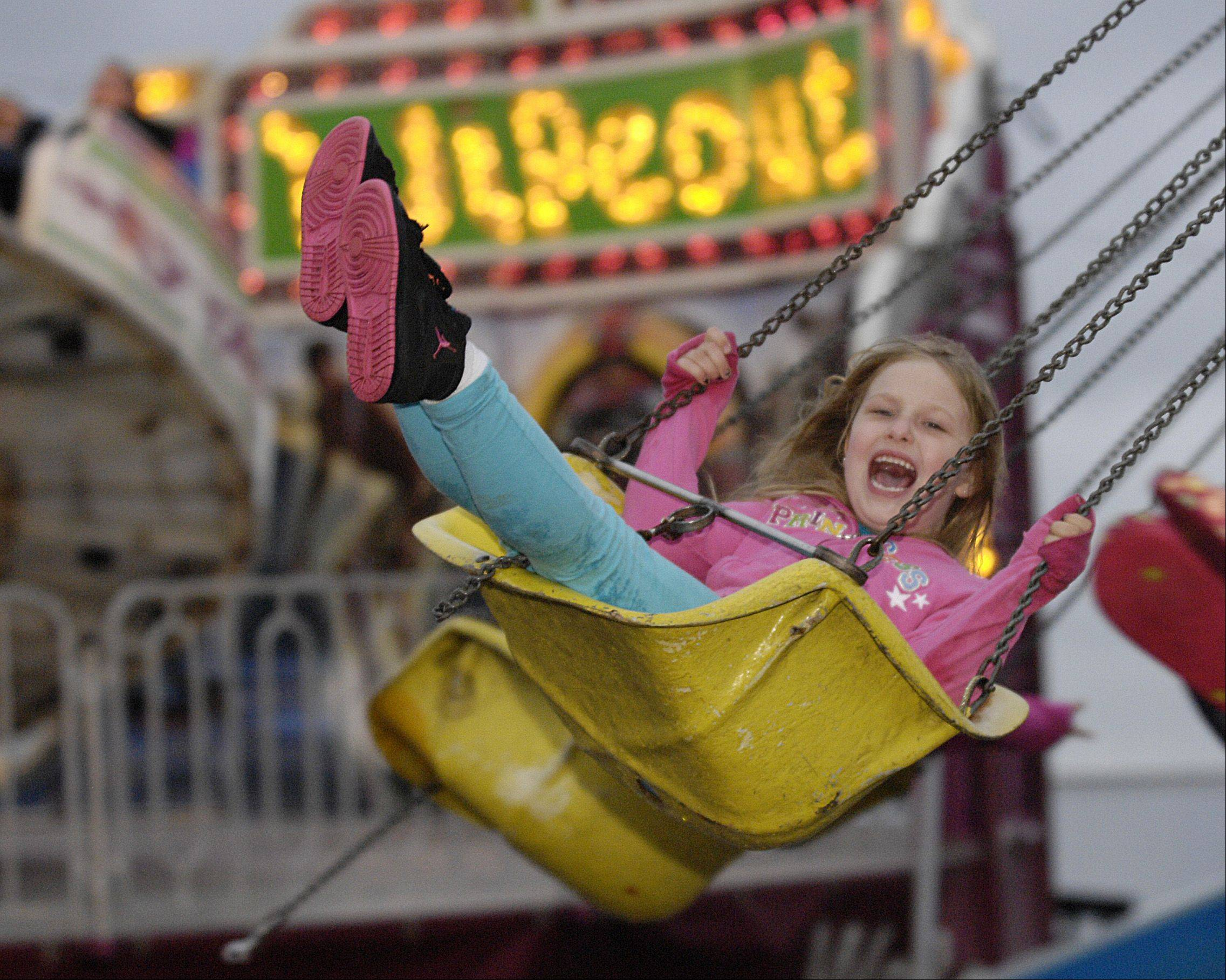 Alexa Fish, 6 of Roselle rides the swings on opening night of the annual Rose Fest in Roselle, Thursday.