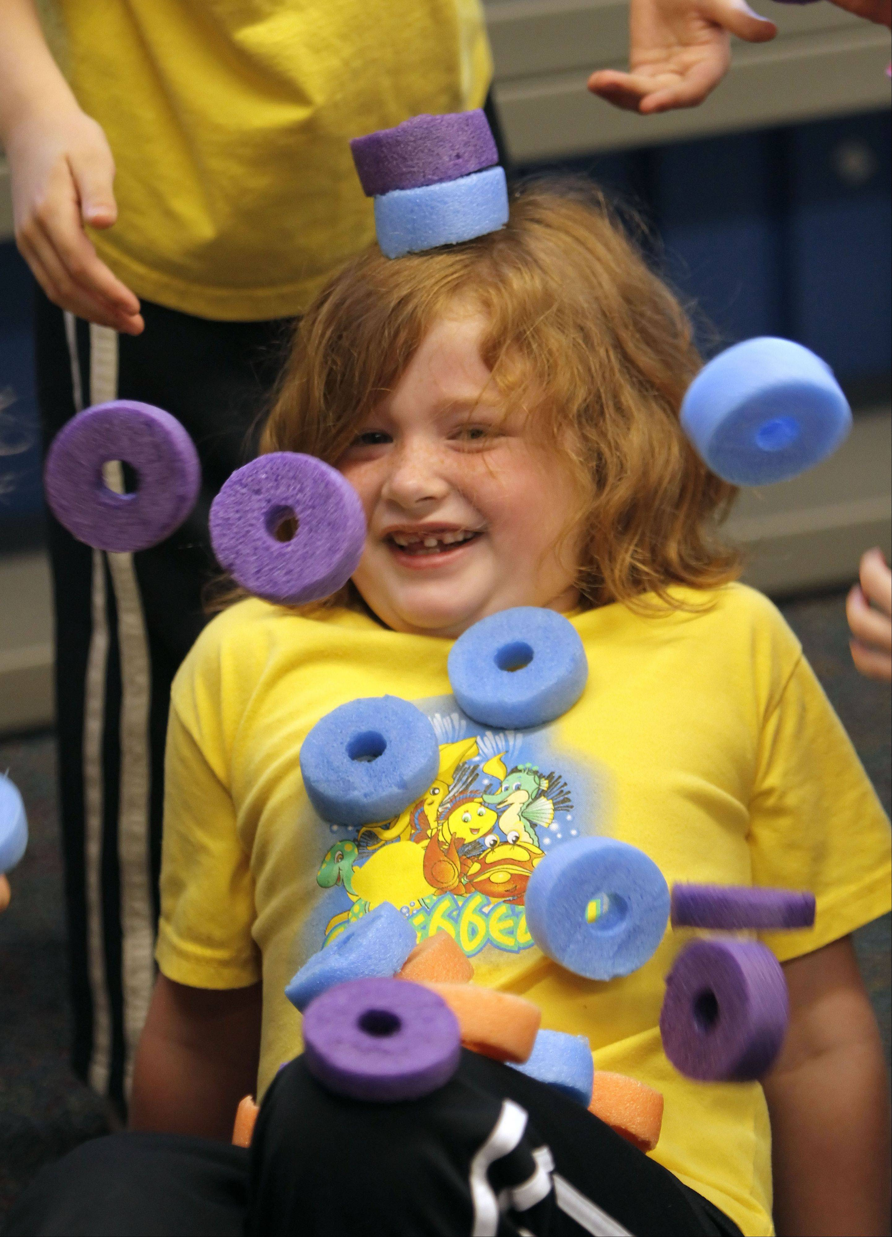 Kindergartner Julia Boggs is covered with rings as kids play a game called statue at Copeland Manor School in Libertyville. The school held their annual field days indoors Thursday because of the rain.