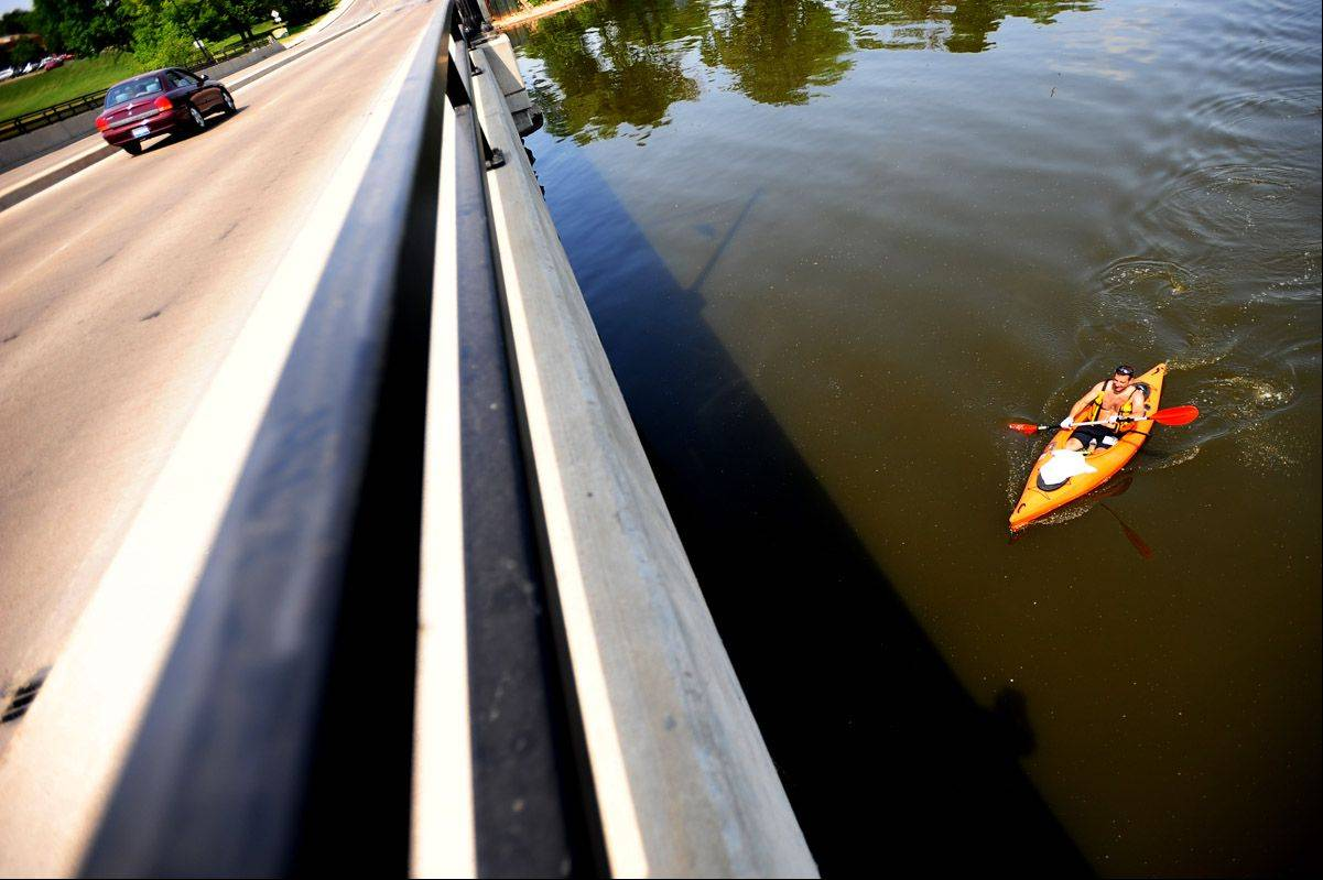 Bob Dickinson of Downers Grove paddles his kayak under a bridge during the Amped Up Adventure Race in Aurora, IL on Sunday.