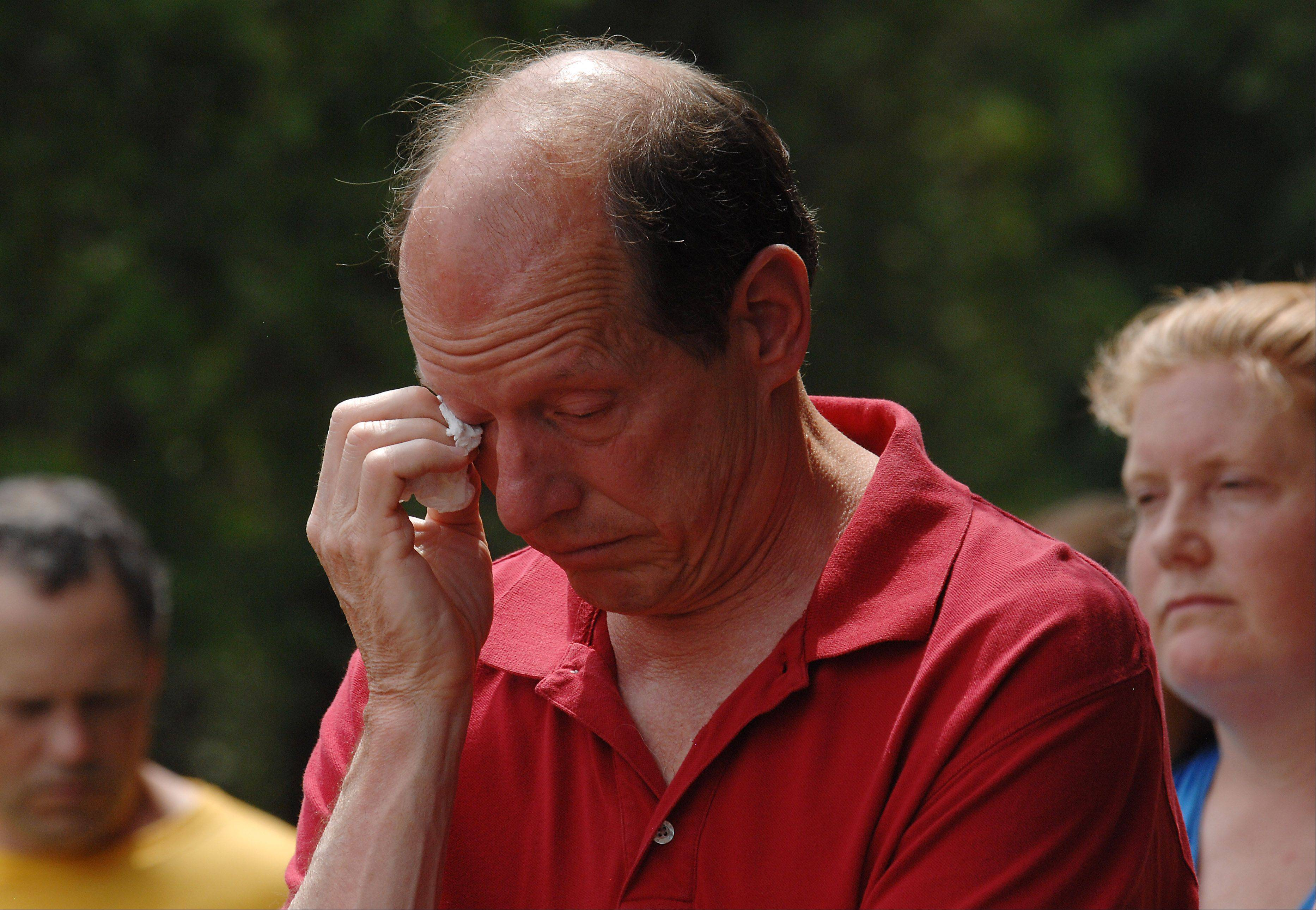 Palatine's Phil Sawicki wipes away tears for his father, George, who died in World War II as officers of Veterans of Foreign Wars Post 7706 honor the fallen at Evergreen Cemetery during the Barrington Memorial Day ceremony on Monday.