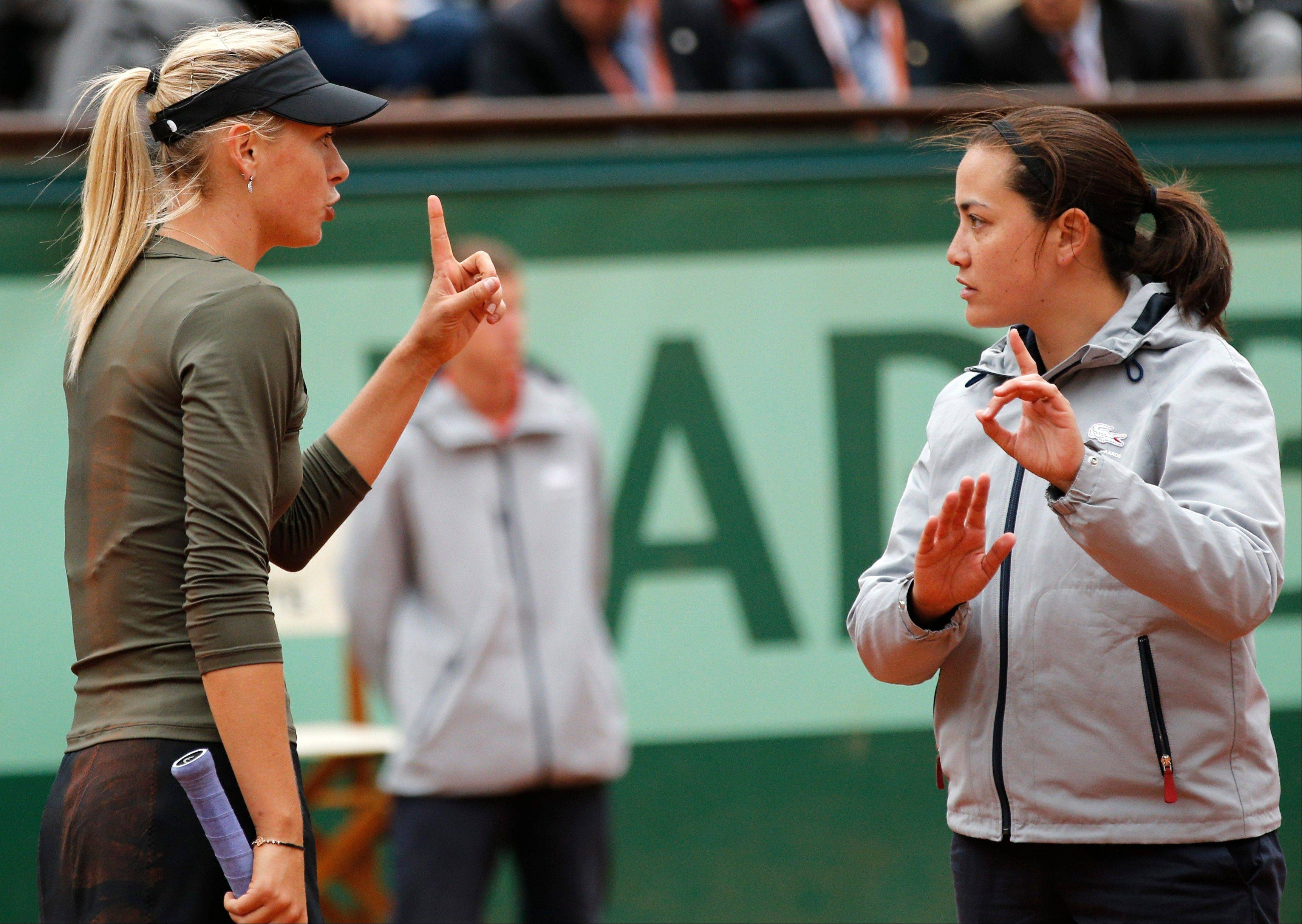 Russia's Maria Sharapova, left, argues with umpire Julie Minori Kjendlie, of Norway, as she plays Czech Republic's Klara Zakopalova during their fourth round match in the French Open tennis tournament Monday at the Roland Garros stadium in Paris.