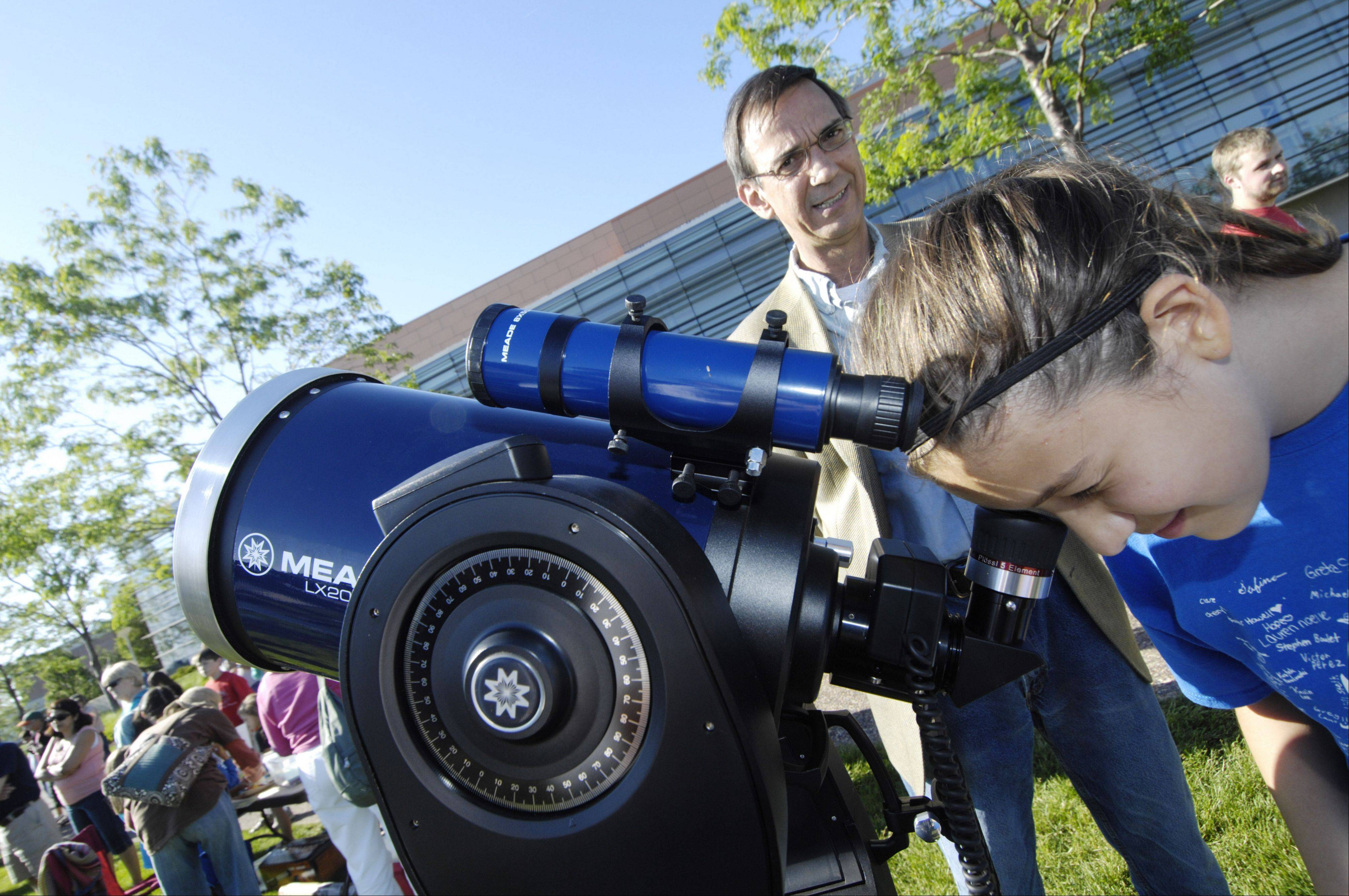 Alexandria Kapko, 12, of Palatine observes Venus crossing the face of the sun Tuesday evening. Palatine attorney James Wotal was there to help people lined up at the telescope find the planet during viewing of the event at Harper College.