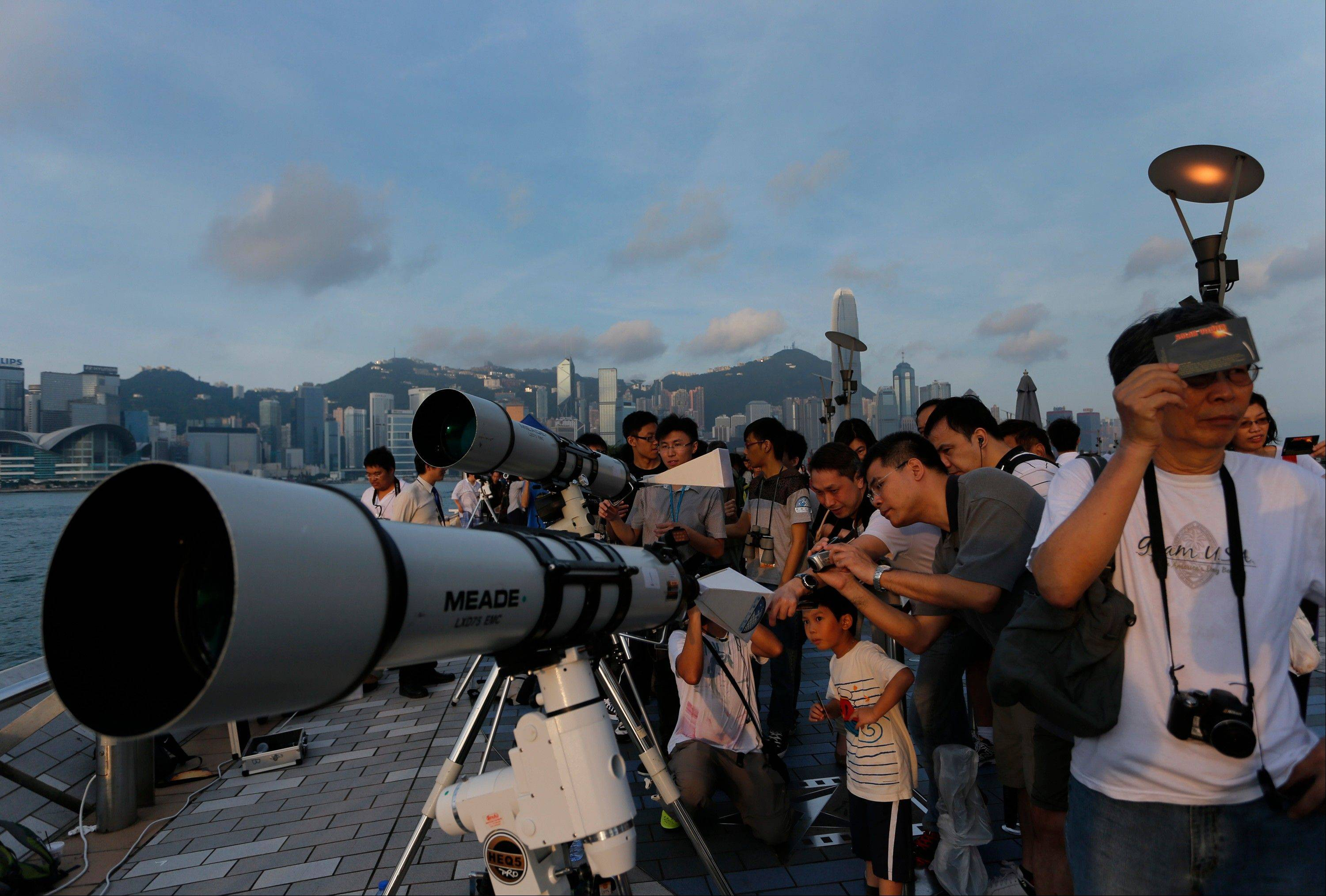 Hong Kong stargazers use telescopes to observe the transit of Venus along the Victoria Habour in Hong Kong Wednesday, June 6, 2012. Stargazers around the world are setting up special telescopes and passing out cardboard eclipse glasses to view the once-in-a-lifetime celestial cameo of Venus passing in front of the sun.