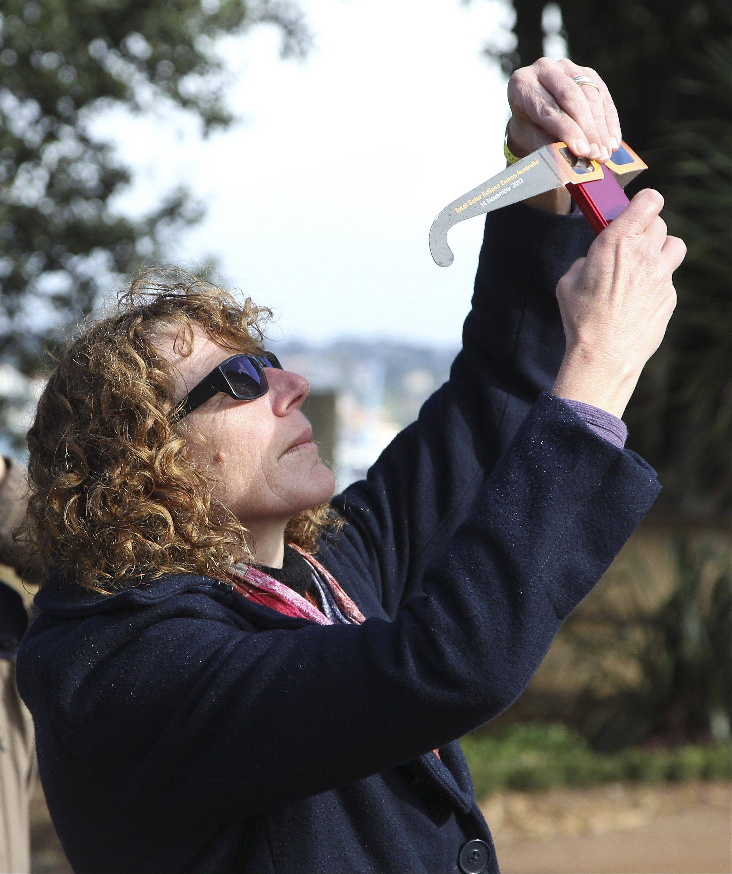 A woman holds a pair of solar viewing glasses to her mobile phone to photograph Venus passing the sun at the Sydney Observatory in Sydney, Australia, Wednesday, June 6, 2012.
