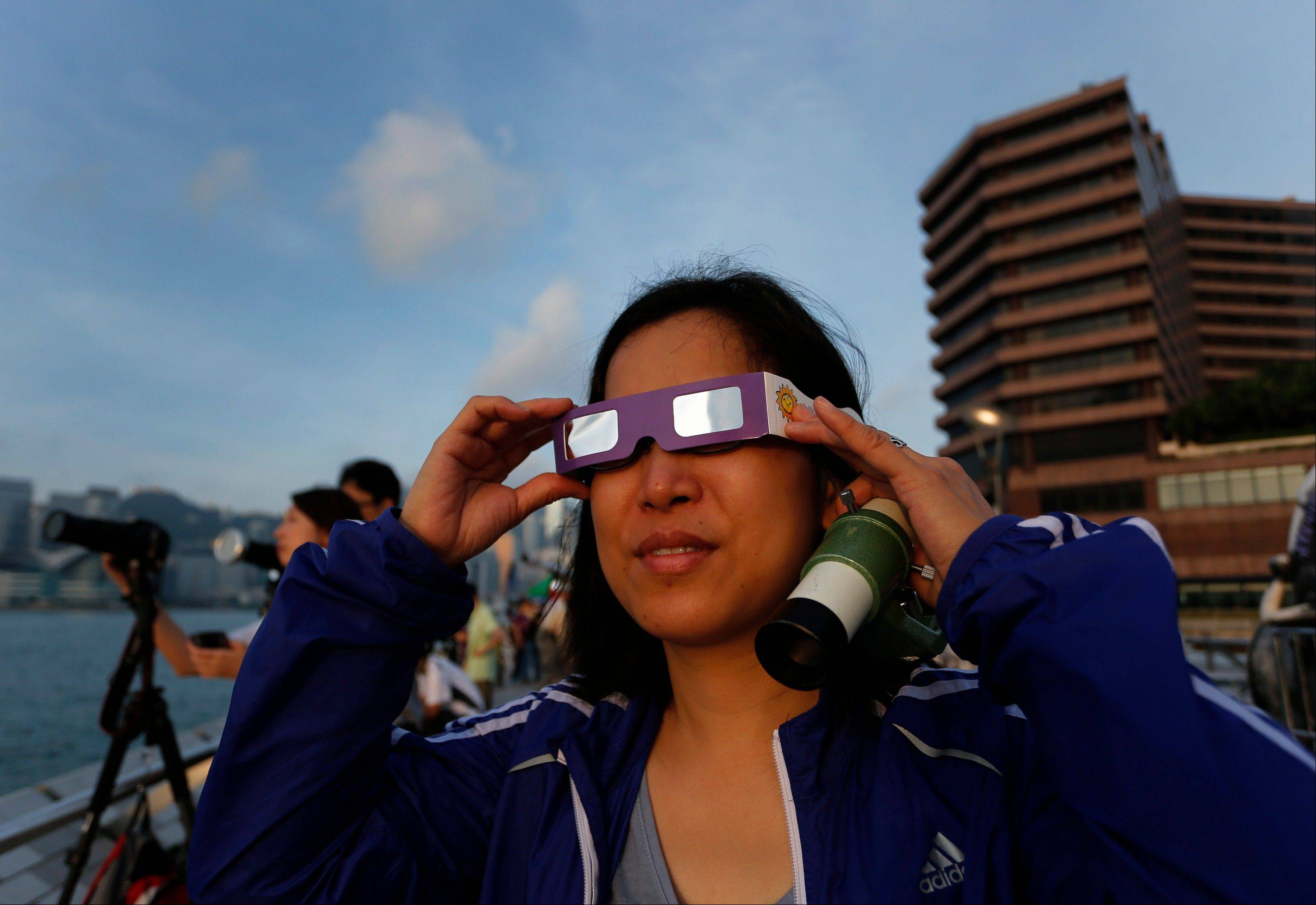 A Hong Kong stargazer uses a special sunglasses to observe the transit of Venus along the Victoria Habour in Hong Kong Wednesday, June 6, 2012. Stargazers around the world are setting up special telescopes and passing out cardboard eclipse glasses to view the once-in-a-lifetime celestial cameo of Venus passing in front of the sun.
