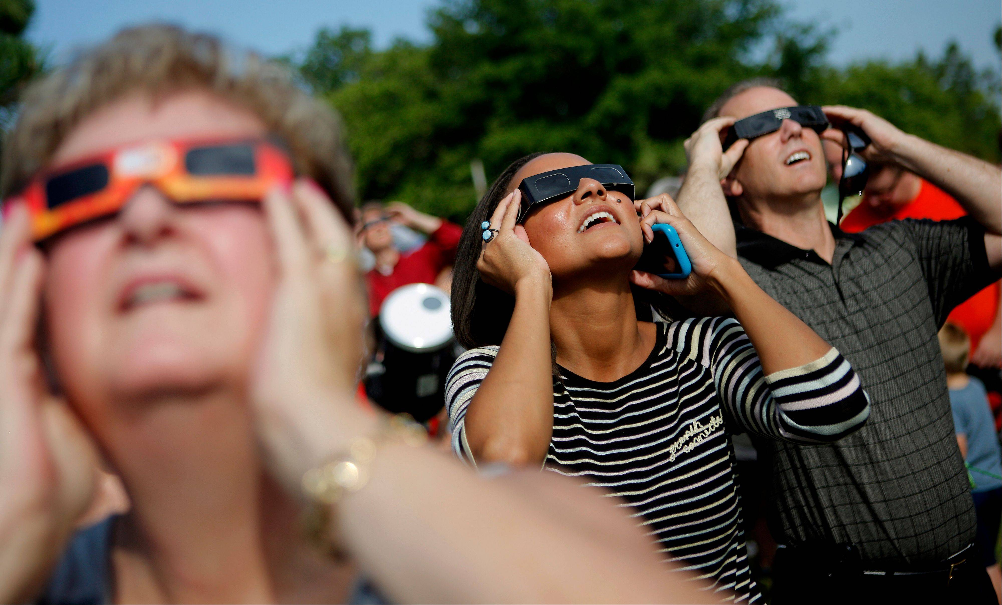 Erin Kozakiewicz, center, and Steve Whelchel, right, use glasses while viewing the transit of Venus in front of the sun with the Oklahoma Astronomy Club's viewing at the Science Museum of Oklahoma on Tuesday, June, 5, 2012.