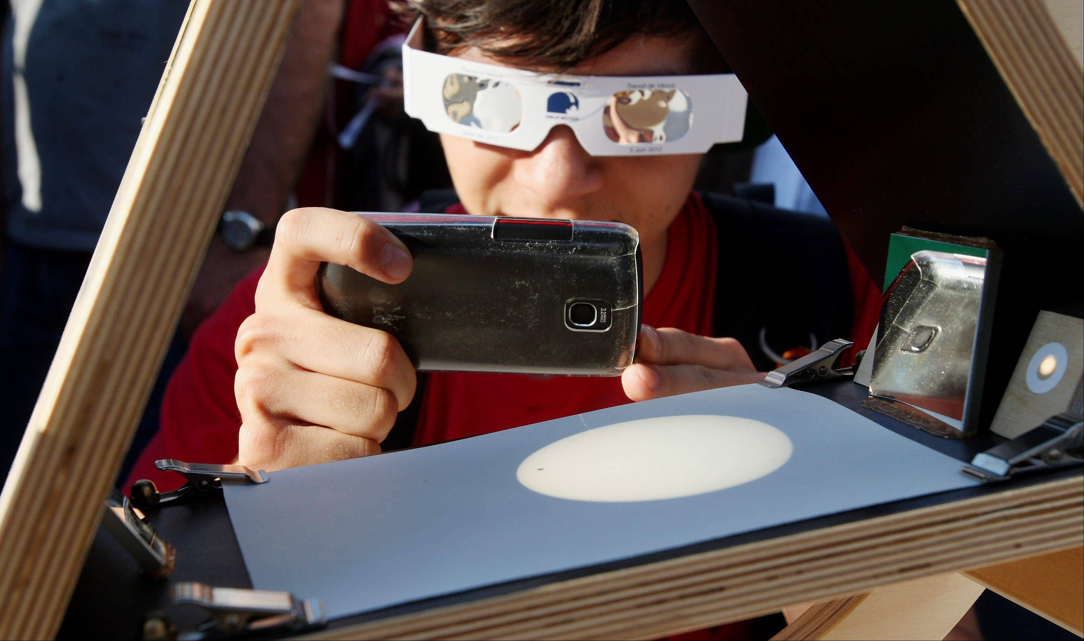 Matt Scott, still wearing protective glasses, tries to take a photo of a projected image of the sun as hundreds of people gather to watch the transit of Venus at the University of Western Ontario in London, Ontario on Tuesday, June 5, 2012. The rare event occurs when the planet Venus moves in front of the sun. The next time this will occur is in 105 years in 2117.
