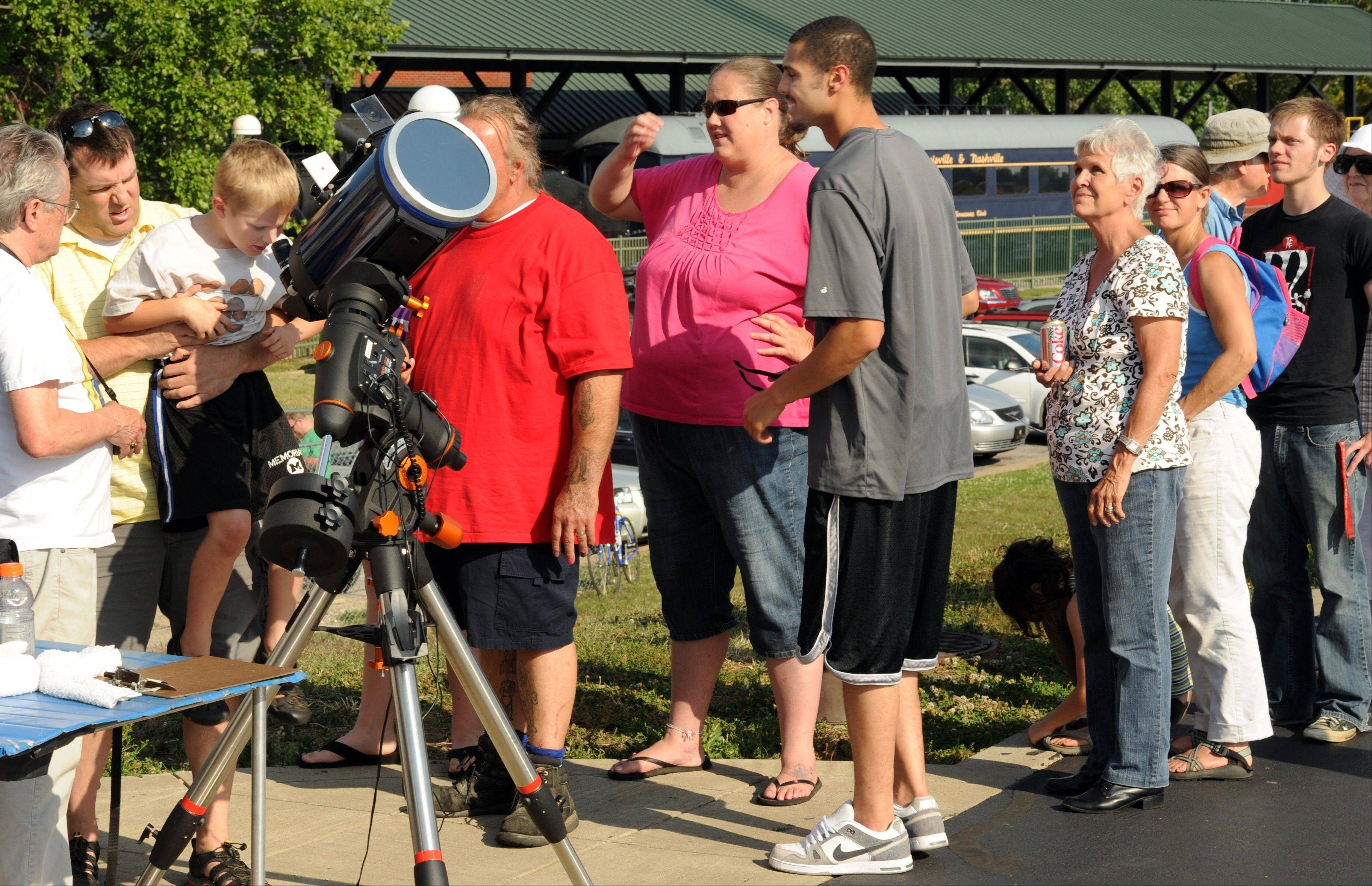 Brian Cunningham, of Evansville, Ind., second from left, holds his son, Teddy, age 7, so he can look through the telescope to see the transit of Venus on Tuesday, June 5, 2012. Cunningham had done the same for his two other sons Zach, 11 and Ben, 9, as they were part of a crowd that gathered along the Ohio River behind the Evansville Museum of Arts, History & Science in Evansville, Ind. to watch Venus as the planet moves in front of the Sun. Members of the Evansville Astronomical Society set up telescopes so people could look at the event.
