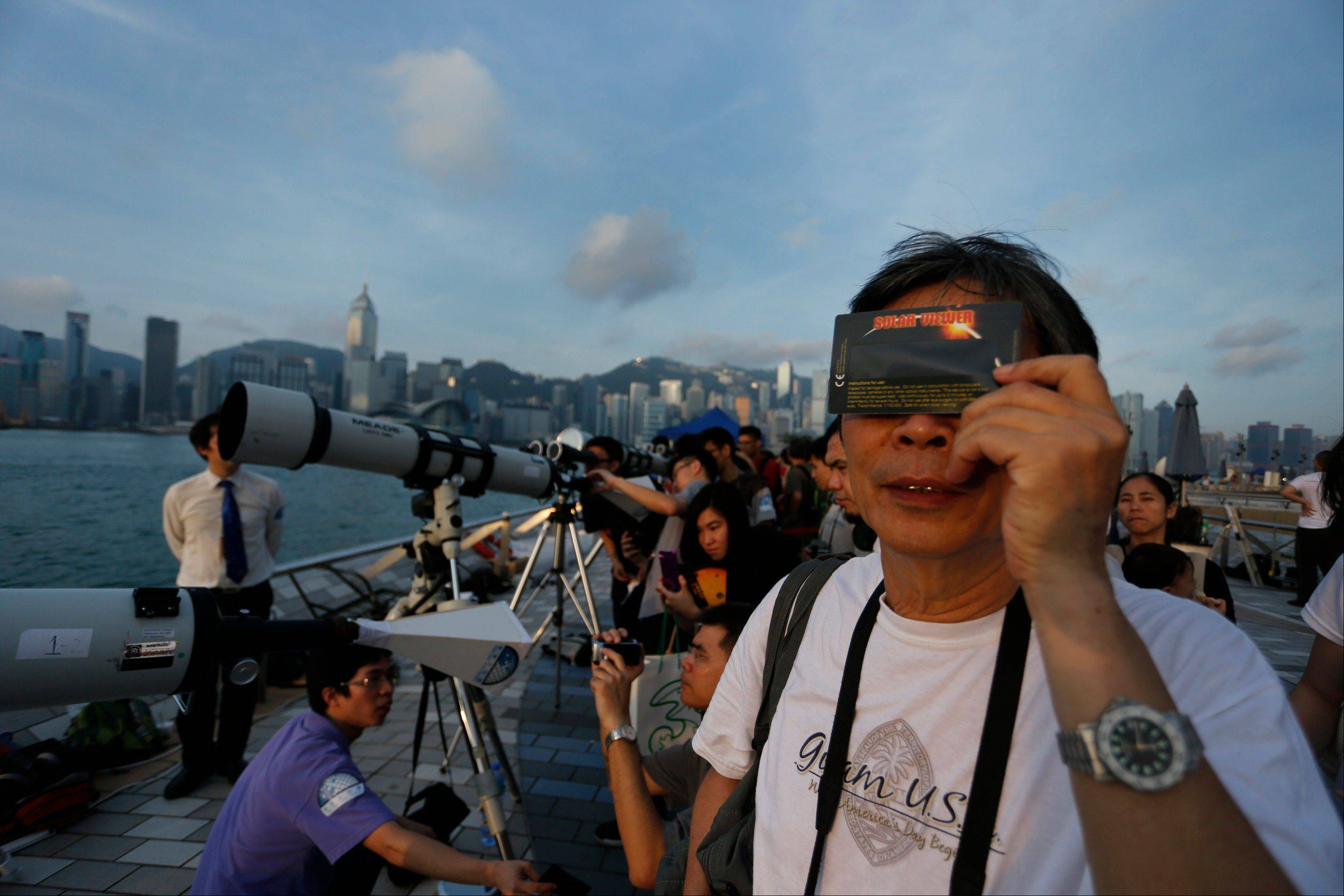 Hong Kong stargazers use telescopes and special sunglasses to observe the transit of Venus along the Victoria Habour in Hong Kong Wednesday, June 6, 2012. Stargazers around the world are setting up special telescopes and passing out cardboard eclipse glasses to view the once-in-a-lifetime celestial cameo of Venus passing in front of the sun.