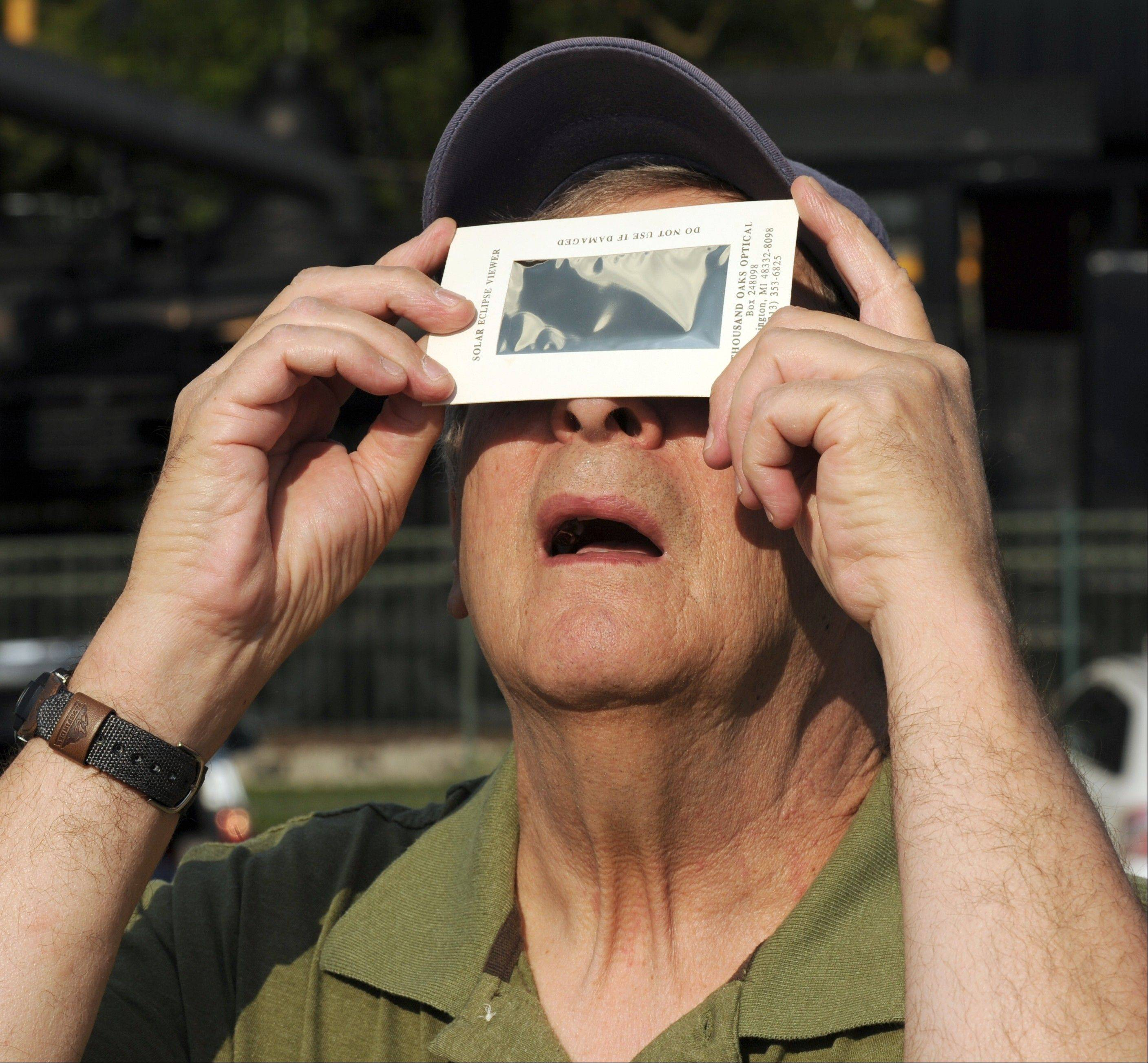 Joseph R. Caruso, of Newburgh, Ind. uses a viewing device made to safely look at solar eclipses as he tries to see the transit of Venus on Tuesday, June 5, 2012. Caruso was one of the people who set up their telescopes along the Ohio River behind the Evansville Museum of Arts, History & Science in Evansville, Ind. to watch as the planet moves in front of the sun. Although some people said they could see the small dot of Venus using this viewer, Caruso was not having any luck.
