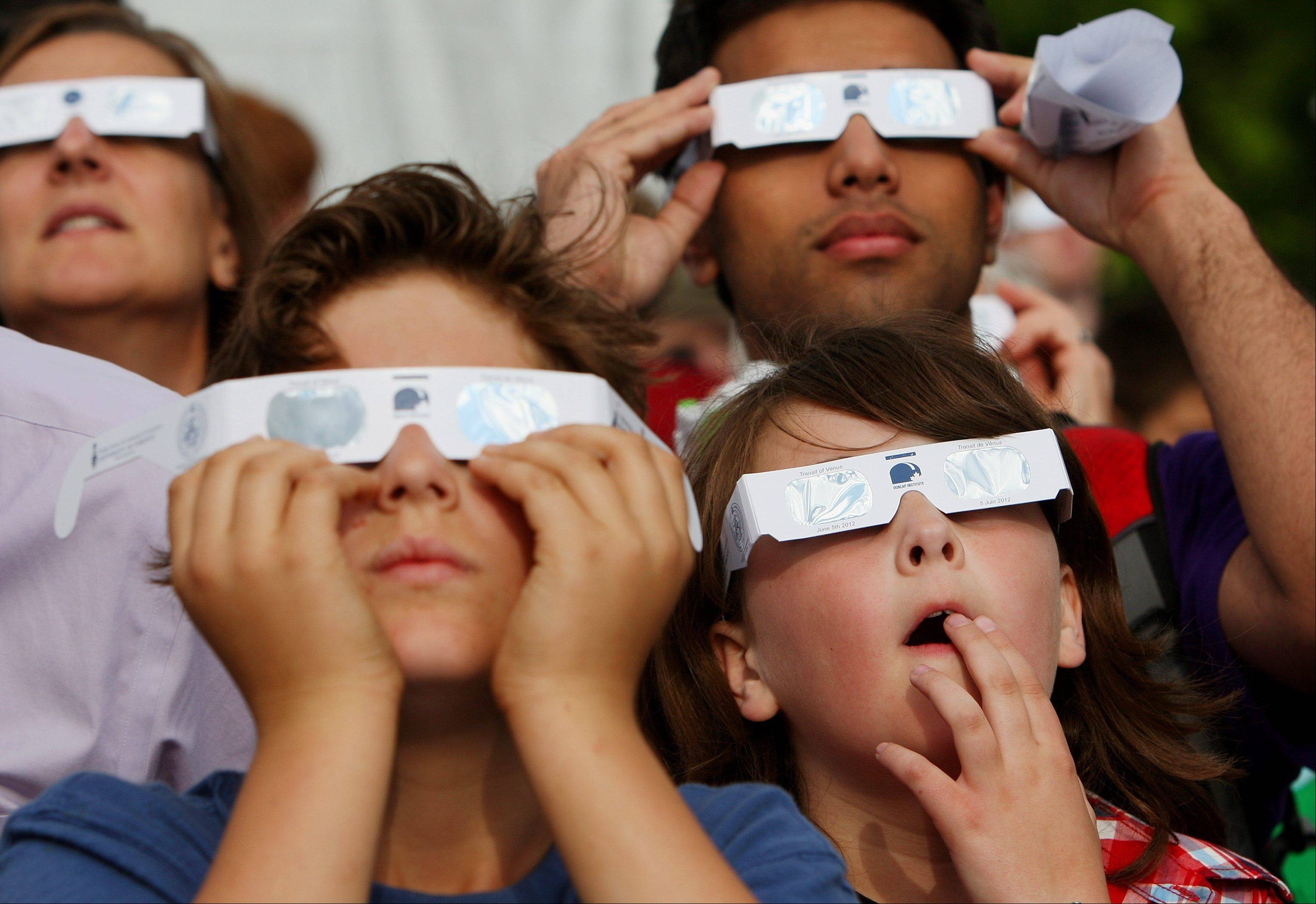 Hundreds of people gather wearing special viewing glasses at the University of Western Ontario in London, Ontario to watch the transit of Venus on Tuesday, June 5, 2012. The rare event occurs when the planet Venus moves in front of the sun. The next time this will occur is in 105 years in 2117.
