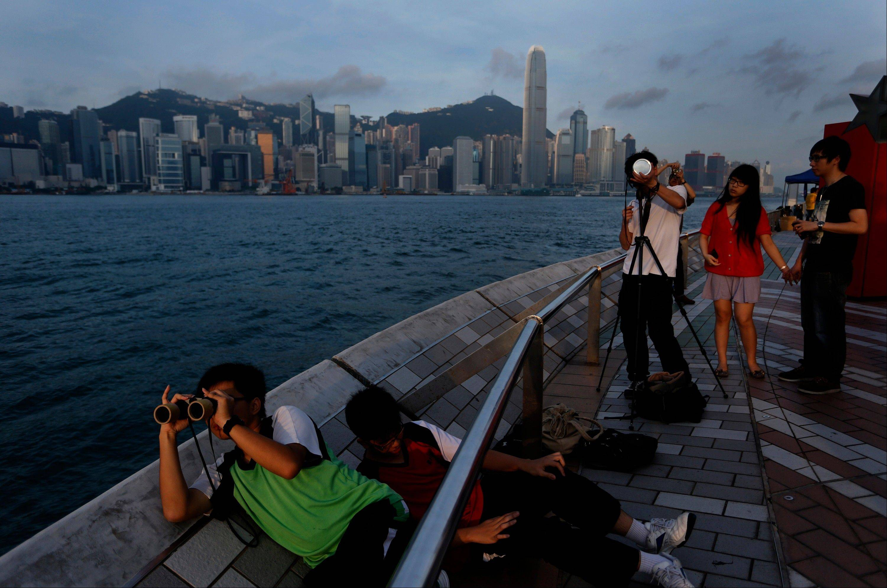 Hong Kong stargazer use special filers on telescope to observe the transit of Venus along the Victoria Habour in Hong Kong Wednesday, June 6, 2012. Stargazers around the world are setting up special telescopes and passing out cardboard eclipse glasses to view the once-in-a-lifetime celestial cameo of Venus passing in front of the sun.