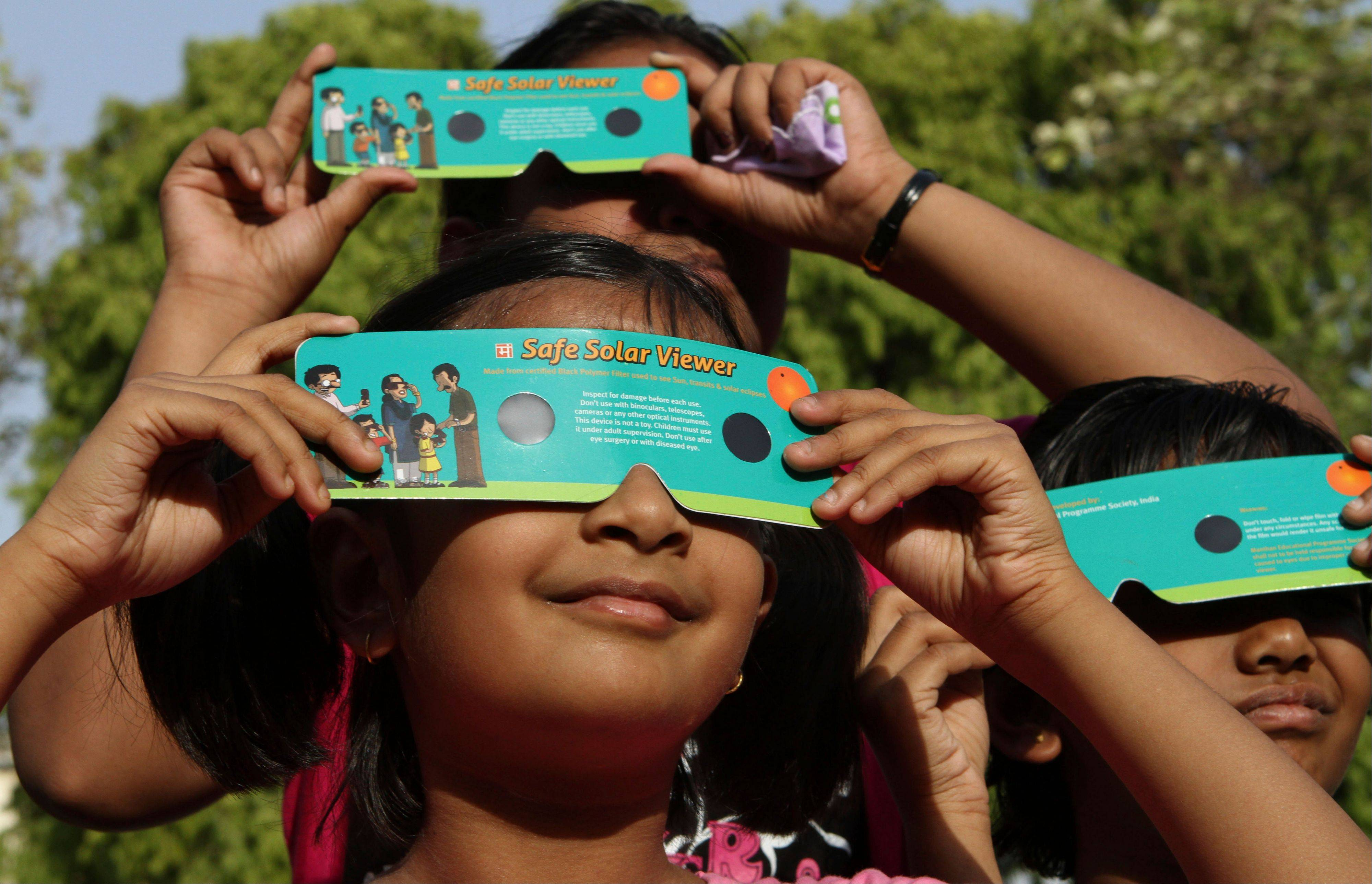 Indian children use cardboard eclipse glasses as they prepare to watch the transit of Venus in Allahabad, India, Tuesday, June 5, 2012. Stargazers around the world are setting up special telescopes and passing out cardboard eclipse glasses to view the once-in-a-lifetime celestial cameo of Venus passing in front of the sun. Venus is Earth's second-closest neighboring planet.