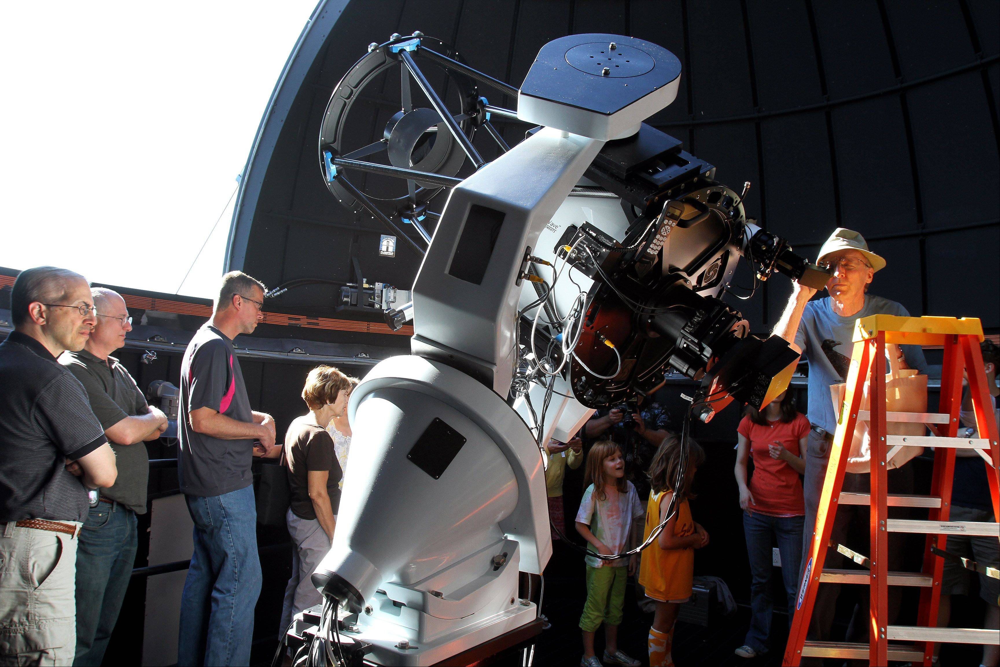 Louis Bowers of Mount Prospect takes a look through the main telescope in the Wheaton College Astronomical Observatory, which opened Tuesday evening for free viewings of the Transit of Venus. Hundreds of people lined up for the event.
