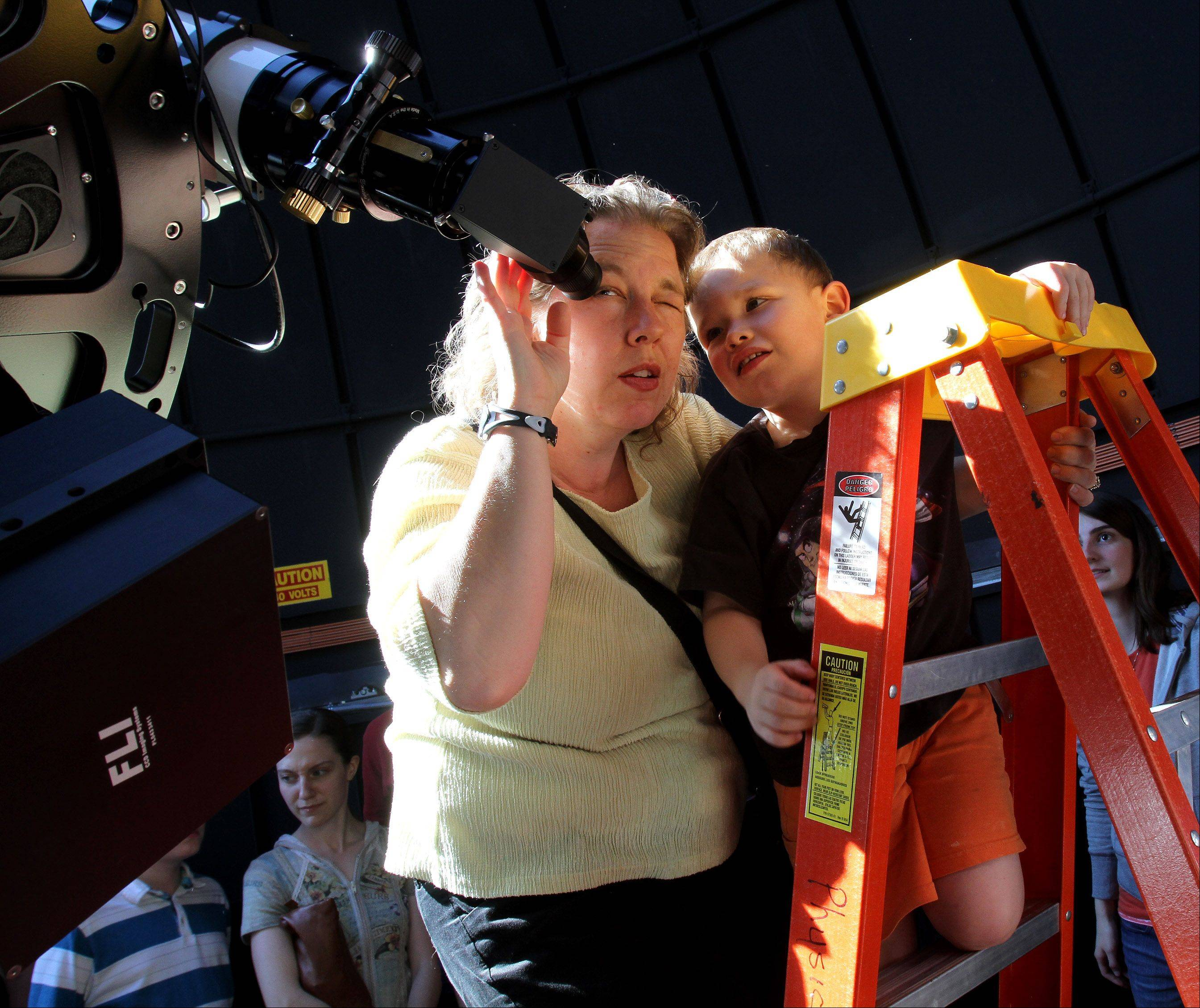 Alta Johnson of Wheaton takes a look through the main telescope with her son Ethan, 4, at the Wheaton College Astronomical Observatory, which opened Tuesday evening for free viewings of the Transit of Venus.