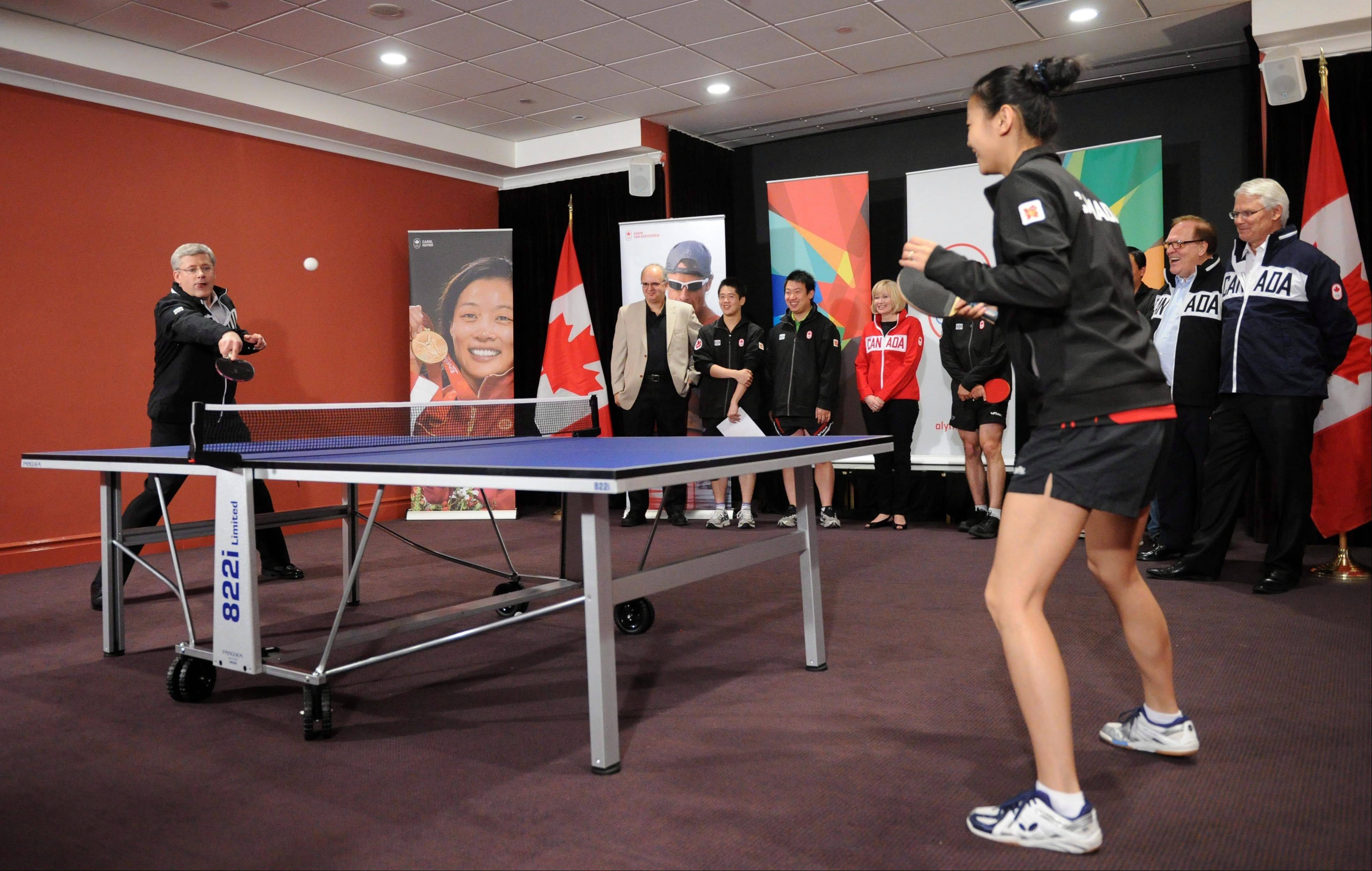 Prime Minister Stephen Harper plays a game of table tennis with Team Canada's Mo Zhang at Canada House in London on Tuesday, June 5, 2012. Harper announced that Canada House would be designated as Canada Olympic House during the 2012 London Olympics.