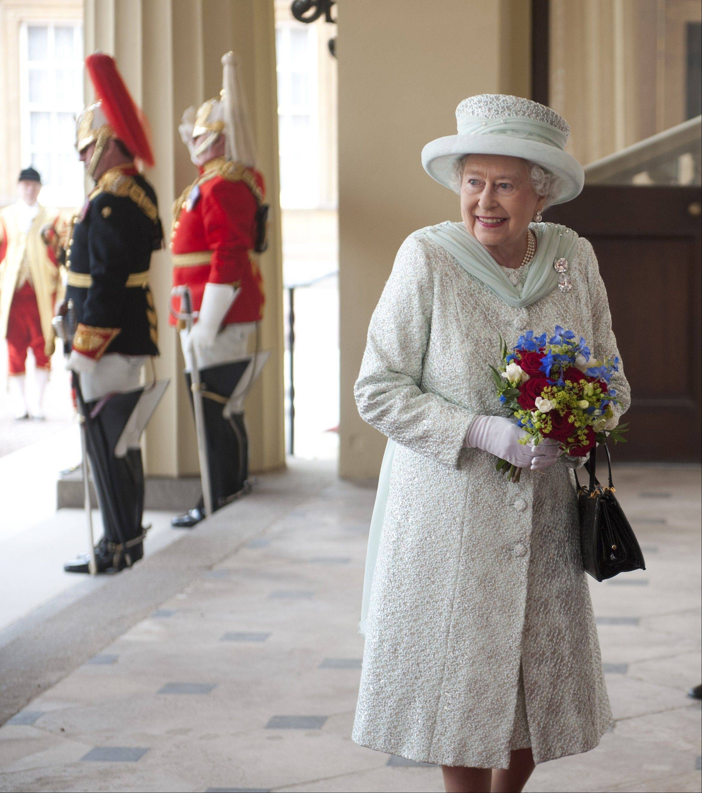 Britain's Queen Elizabeth II holds a bouquet of flowers as she returns to Buckingham Palace after attending a service of thanksgiving and a lunch in honour of the Diamond Jubilee in London,Tuesday June 5, 2012.