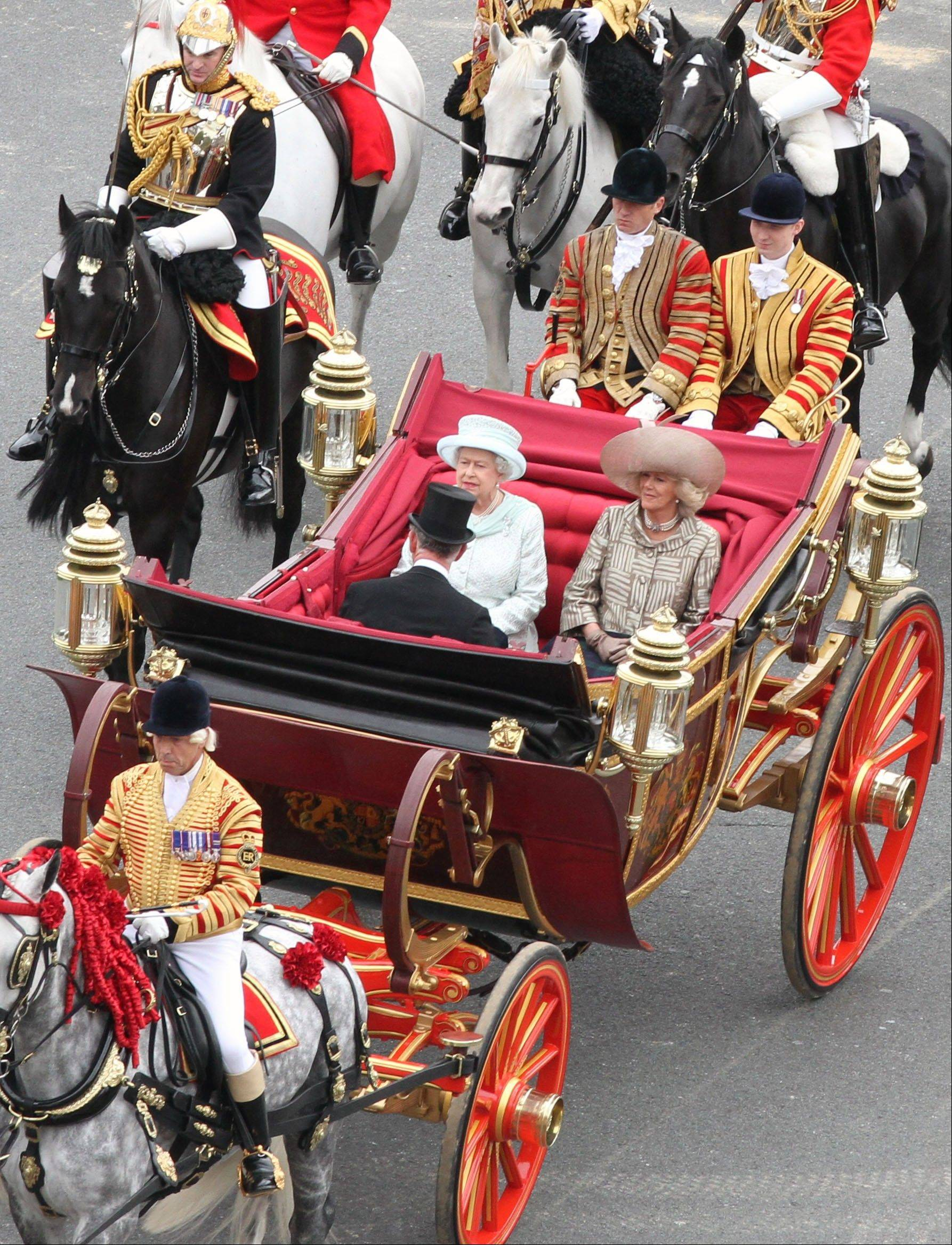 Britain's Queen Elizabeth facing camera left, with Prince Charles and Camilla Duchess of Cornwall, ride in a carriage as they head for Buckingham Palace in a carriage procession in London Tuesday June 5, 2012. The carriage procession is part of a four-day Diamond Jubilee celebration to mark the 60th anniversary of Queen Elizabeth II accession to the throne .