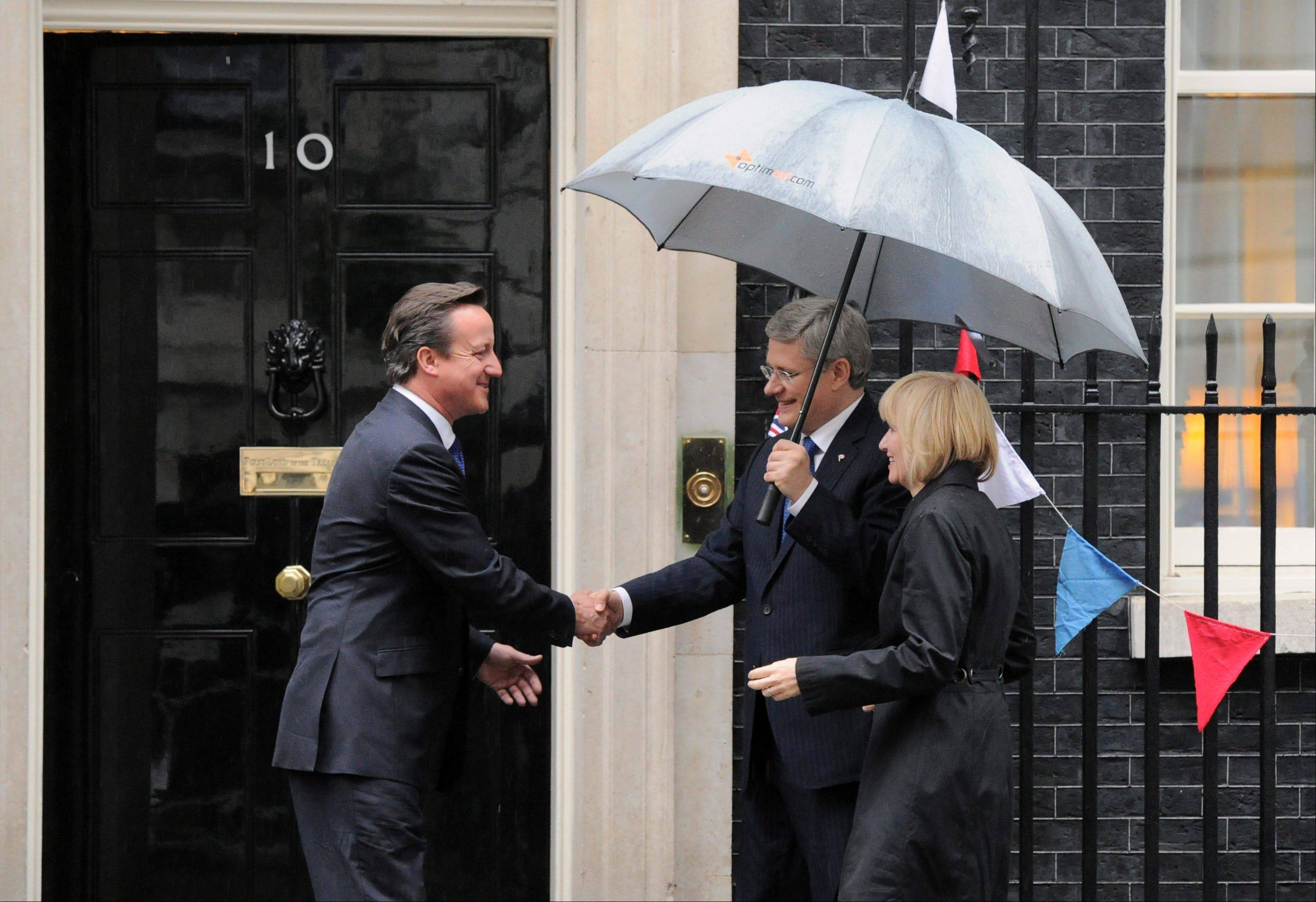 Prime Minister Stephen Harper and wife Laureen, are greeted by British Prime Minister David Cameron as they arrive to 10 Downing Street in London on Tuesday, June 5, 2012.