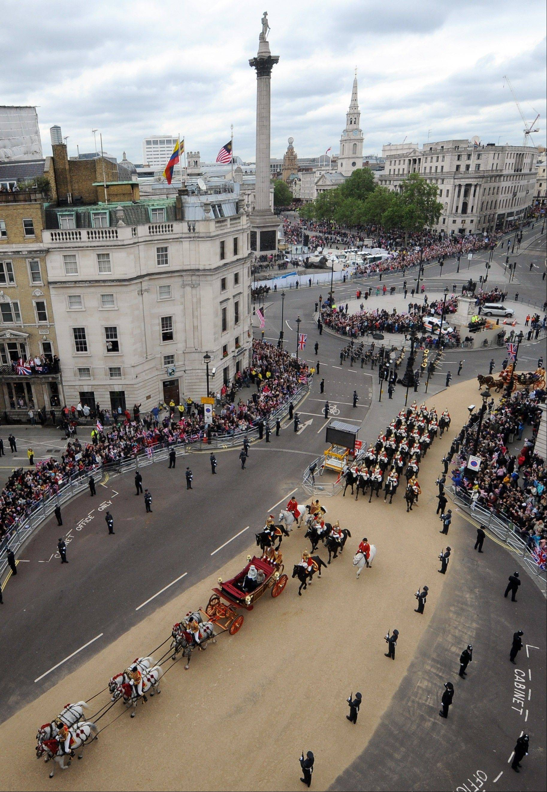 Britain's Queen Elizabeth II, Prince Charles and Camilla Duchess of Cornwall, travel in a carriage through Trafalgar Square, London on route to Buckingham Palace during the Diamond Jubilee celebrations. Tuesday June 5, 2012. Nelson's Column is seen in the background.