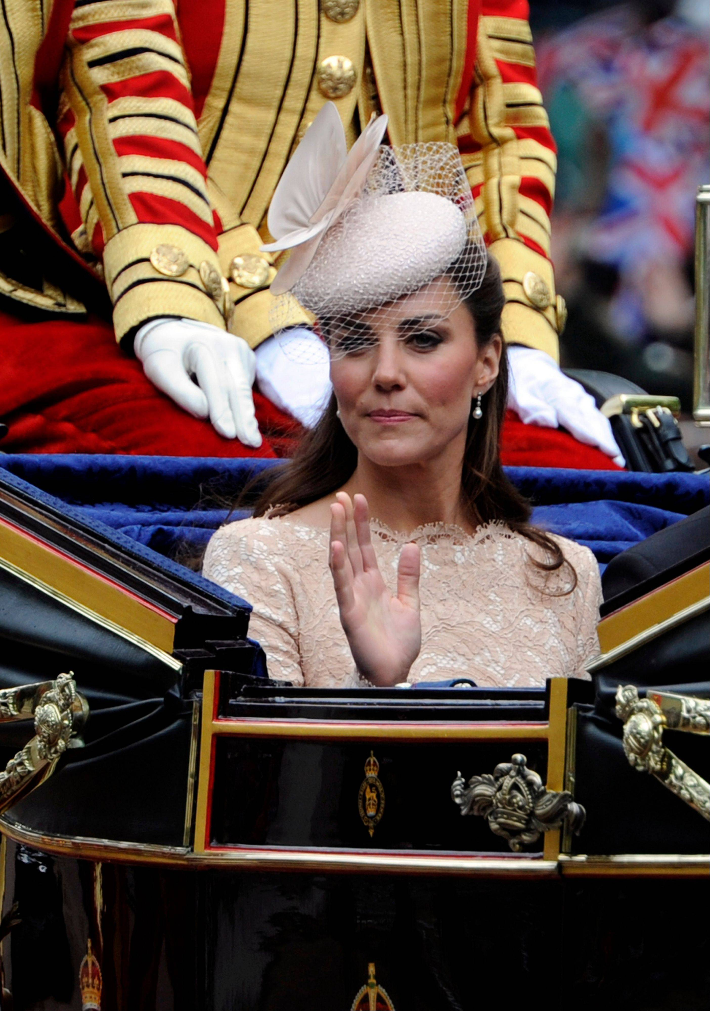 Kate Duchess of Cambridge waves as she passes along The Mall as part of a four-day Diamond Jubilee celebration to mark the 60th anniversary of Queen Elizabeth II accession to the throne, London, Tuesday, June, 5, 2012.