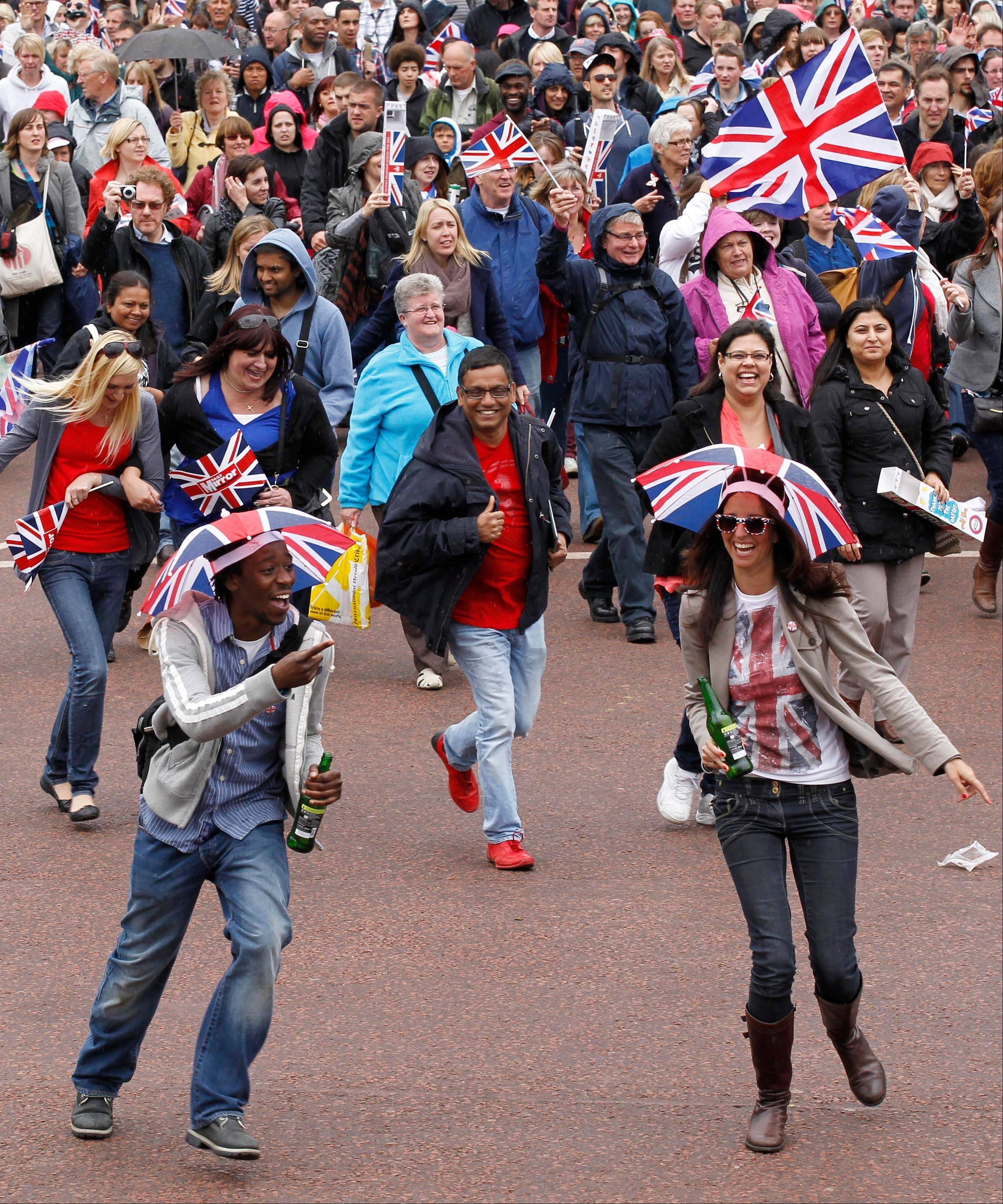Two revelers among thousands rush up the Mall to the gate of Buckingham Palace in London to watch Britain Queen Elizabeth II appear on the palace balcony as part of a four-day Diamond Jubilee celebration to mark the 60th anniversary of Queen Elizabeth II accession to the throne, Tuesday, June 5, 2012.
