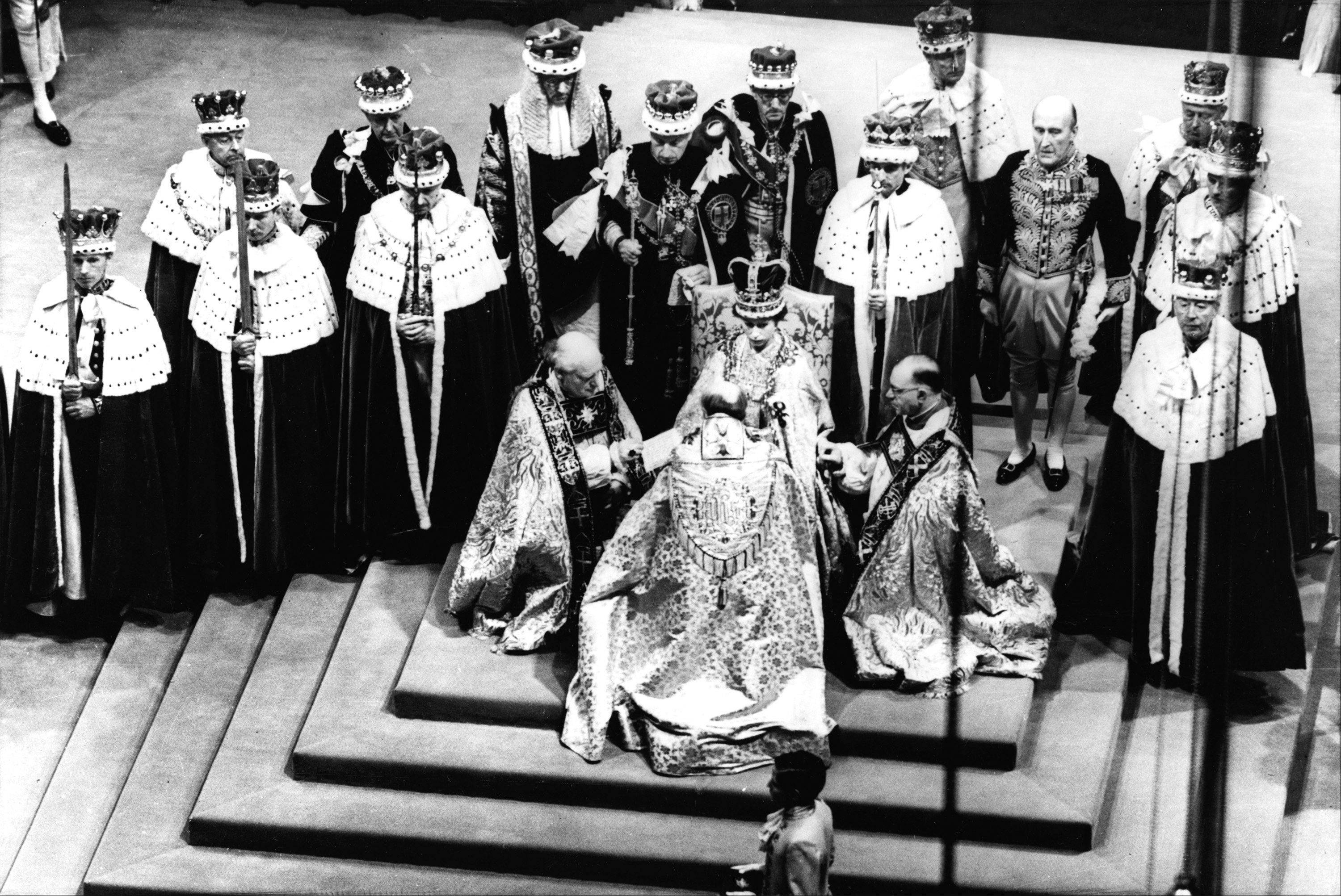 In this June 2, 1953, photo, Britain's Queen Elizabeth II, seated on the throne, receives the fealty of the Archbishop of Canterbury, back to camera at center, the Bishop of Durham, left and the Bishop of Bath and Wells, during her coronation in Westminster Abbey, London.